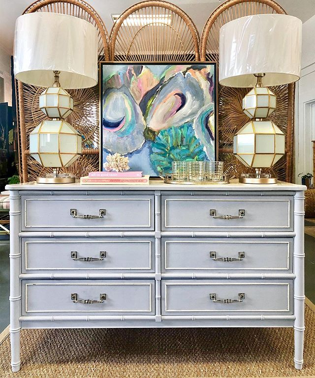 """Will we ever get over this faux bamboo craze? Definitely not, especially if it's a pretty periwinkle piece like this one! - $450 (51.5"""" W x 19"""" D x 32"""" H) • Geometric Cream Glass + Brass Table Lamps - $650/pair • """"Bivalve 7"""" oil on canvas by Cathy Lumpkin - $550 (24"""" x 24"""") . . . #fauxbamboo #bamboo #coastalstyle #coastalliving #coastallife #style #homeinspo #bamboofurniture #colorful #charleston #oysters #oysterart"""