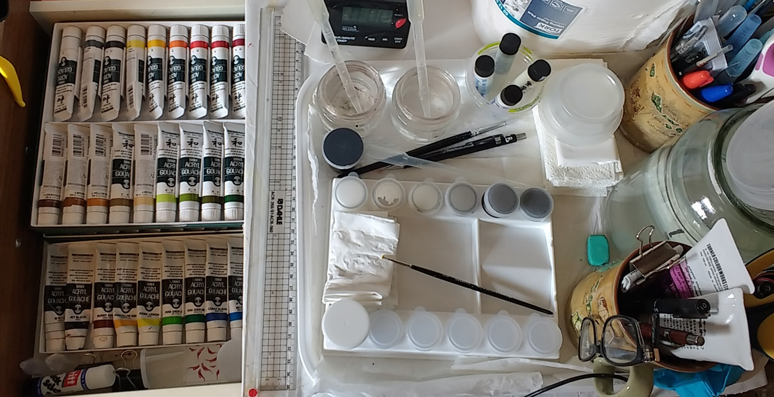 Image description; a selection of paining equiptment laid out on a worktop