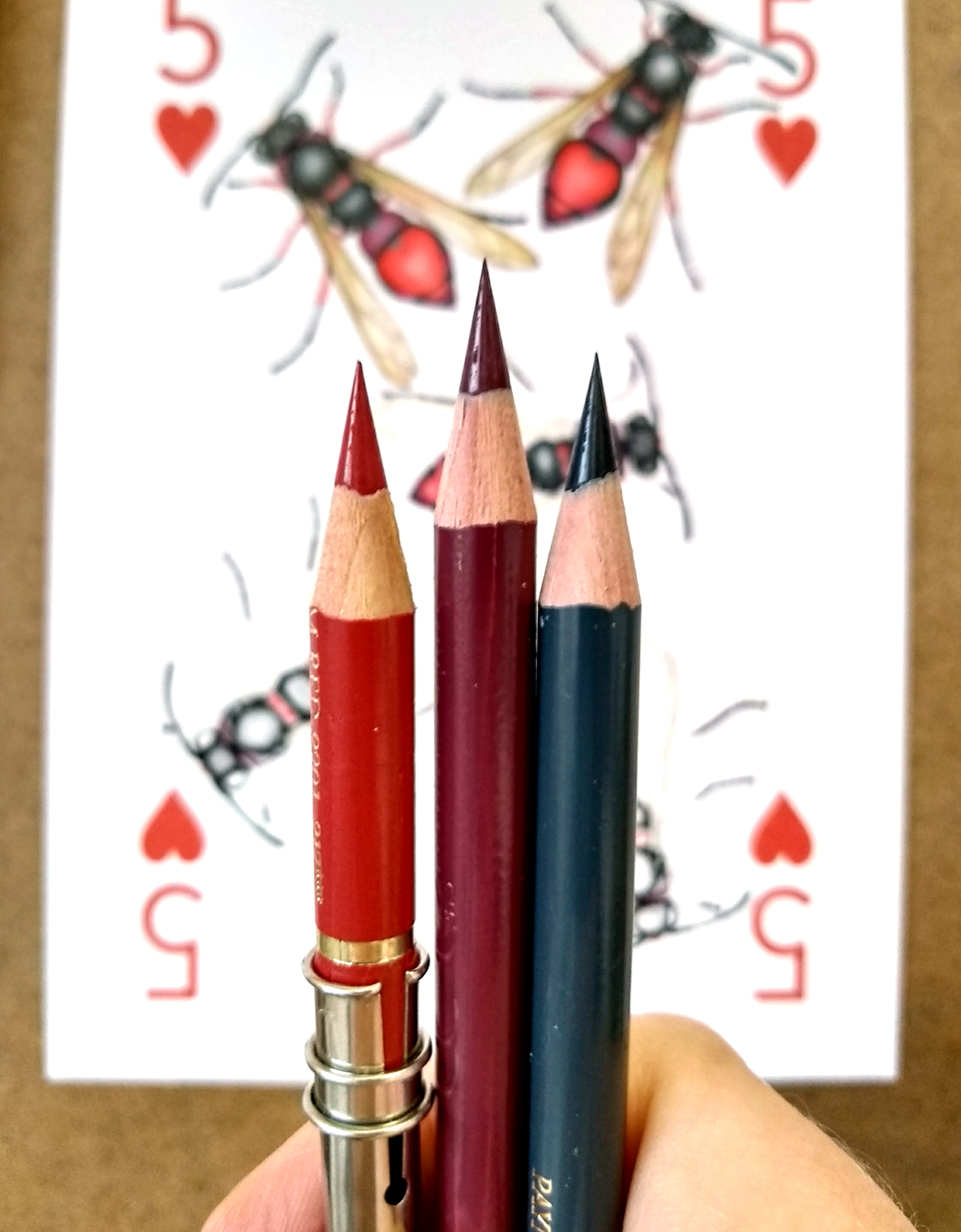 Image description; three very sharp pencils being held up in front of a drawing board.