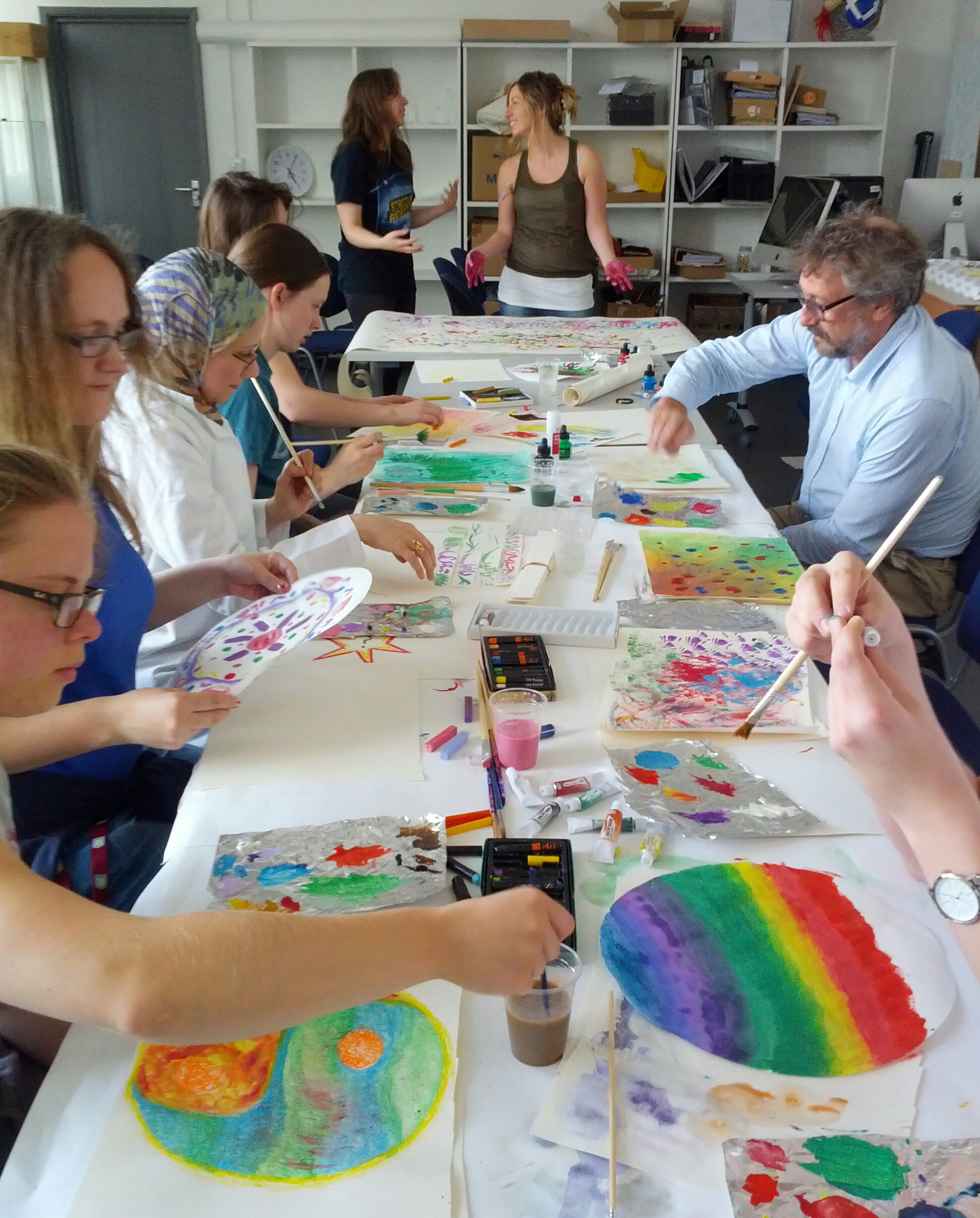 Image description; scientists painting brightly coloured artworks in a workshop