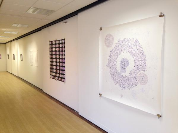 The view down a gallery wall, where large ink patterns and pattern arrays are displayed