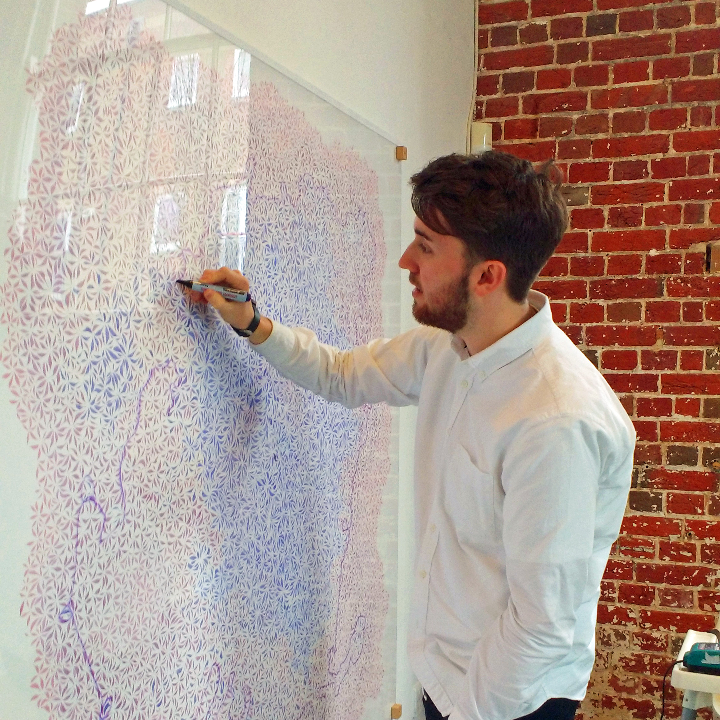 Image description; a person in an art gallery drawing over a large abstract pattern in dry wipe pen. The pattern is under a perspex sheet, so the pen can be wiped off afterwards