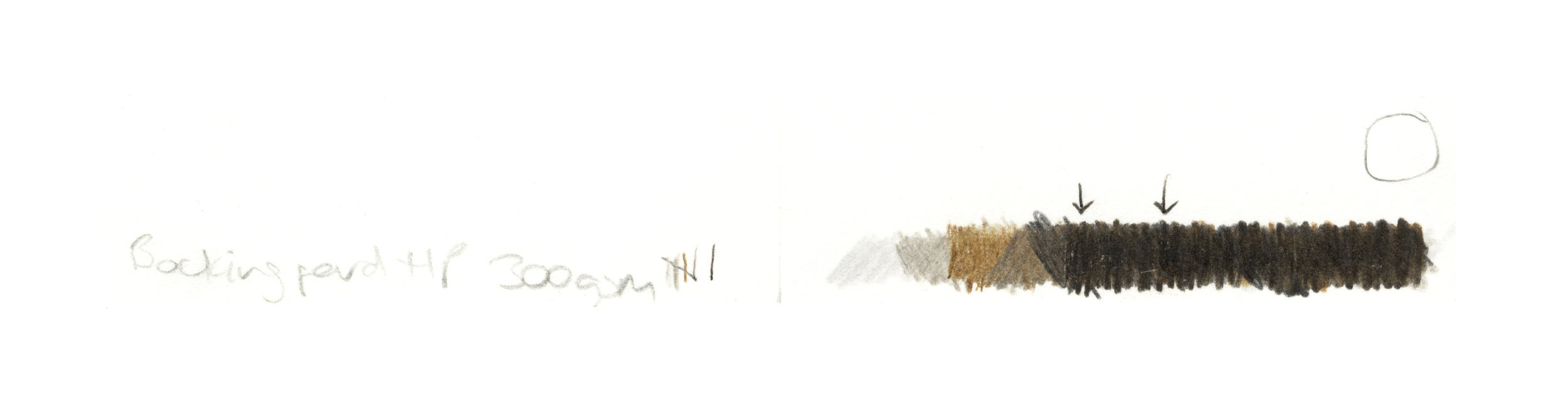 Paper tests for the Bockingford hot press paper, showing test layers of colourpencil shading, and arrows marking where the surface of the paper has fluffed up.   [Image description; grey, brown, & black markings on a thin strip of paper, made to test the papers quality]