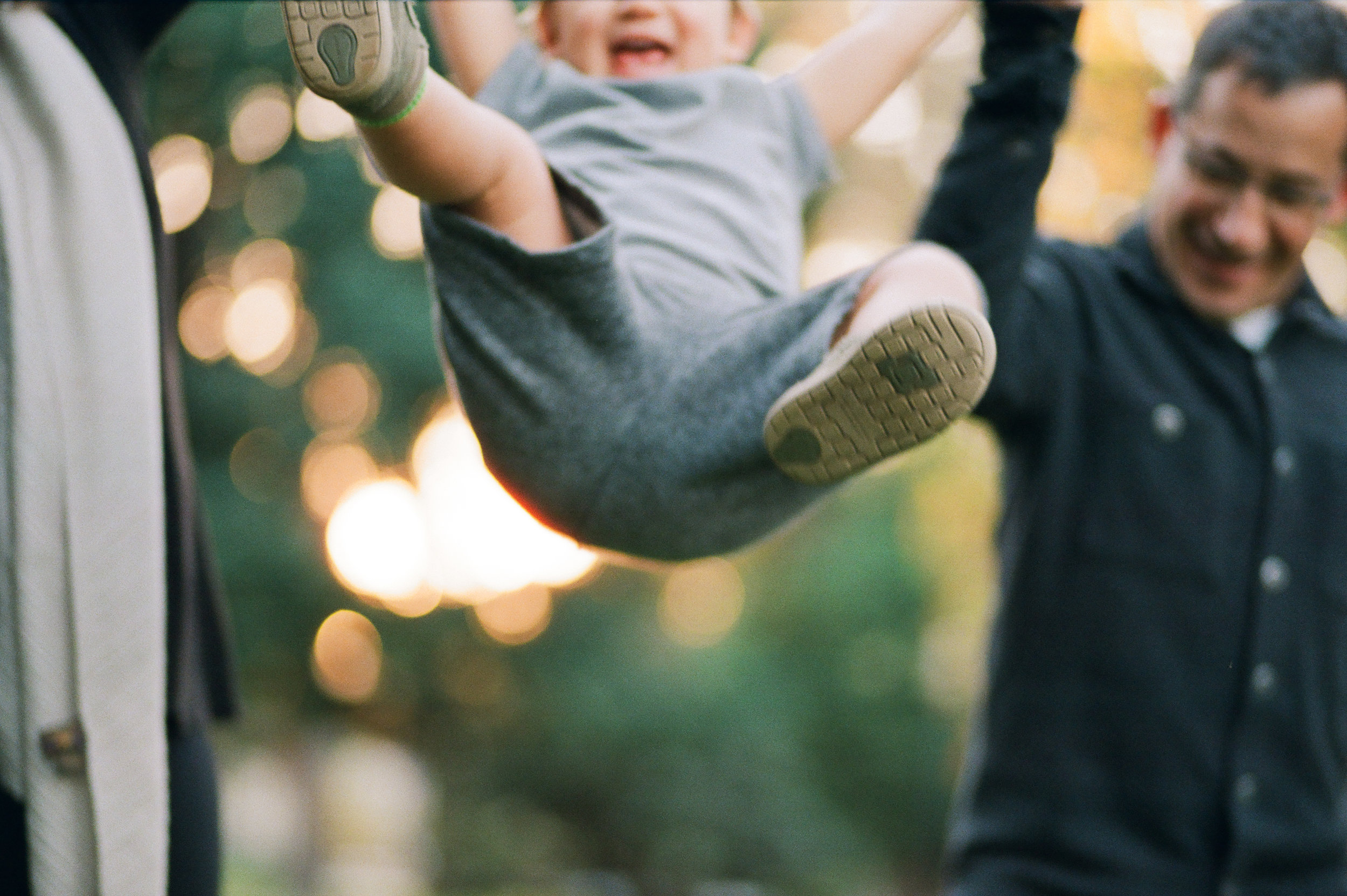 Boy swinging with parents in Sacramento by Rachel Sima Photography