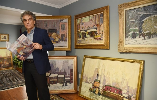 """Louis Gagliardi of Vaughan is seen holding the newly published book detailing the life and work of Peter Clapham Sheppard (1879-1965). In the background, Sheppard's """"forgotten"""" paintings can be seen. - Steve Somerville/Metroland"""