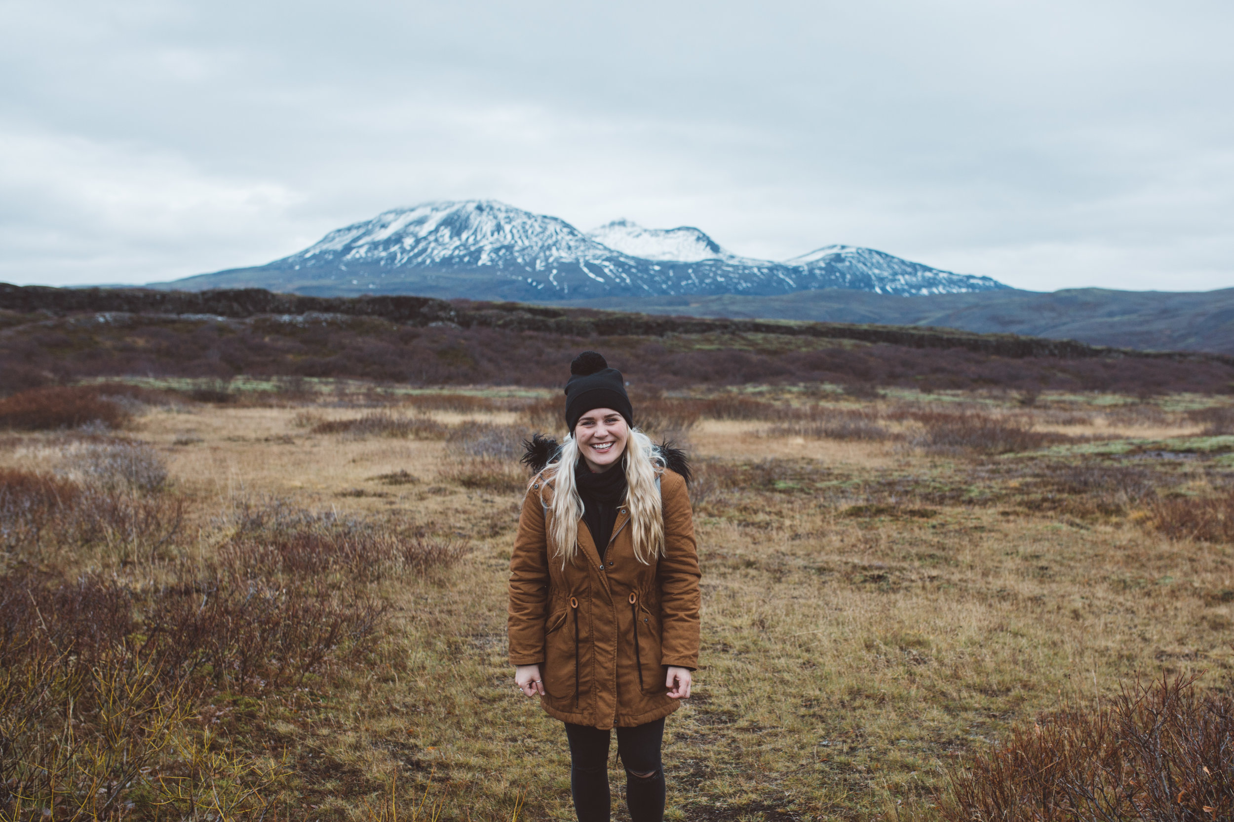 fun and natural wedding photographer standing laughing in the landscape of iceland