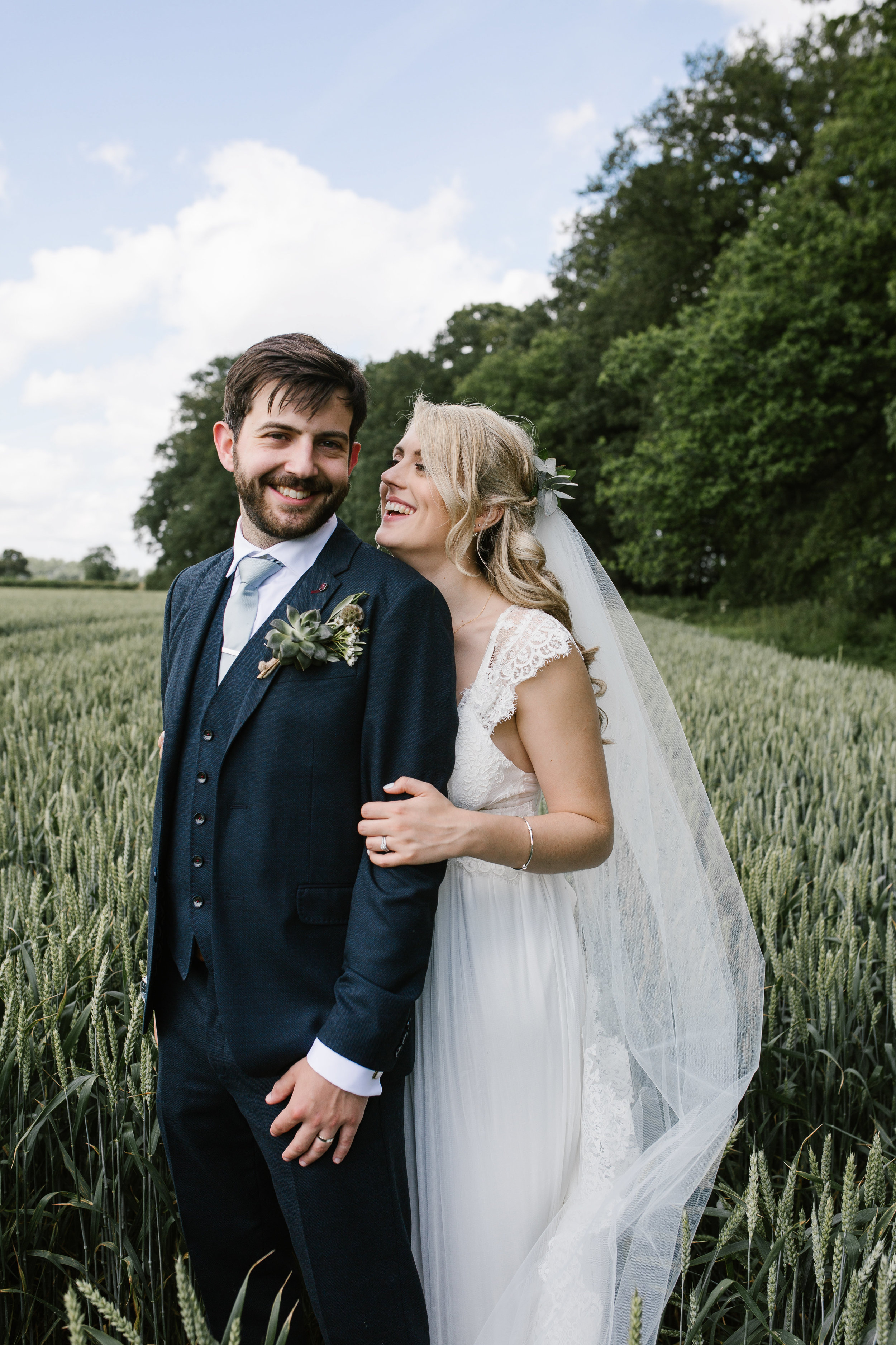 bride and groom happily laughing together in crop field after their wedding ceremony at woodland bluebell in the cotswolds- wedding photography in the cotswolds