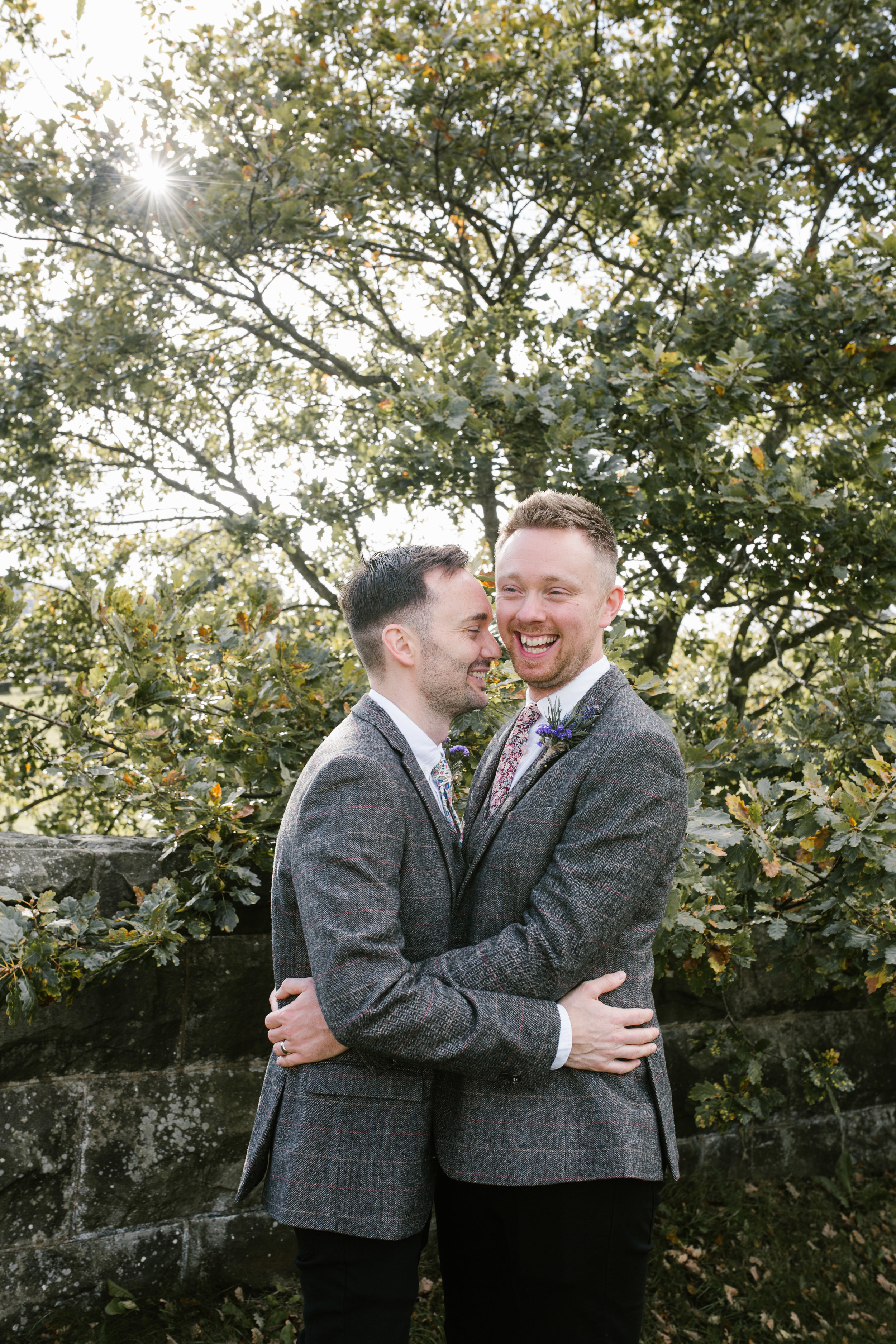 gay couple hugging and laughing together after they have got married at tower hill barns- tower hill barns wedding photographer
