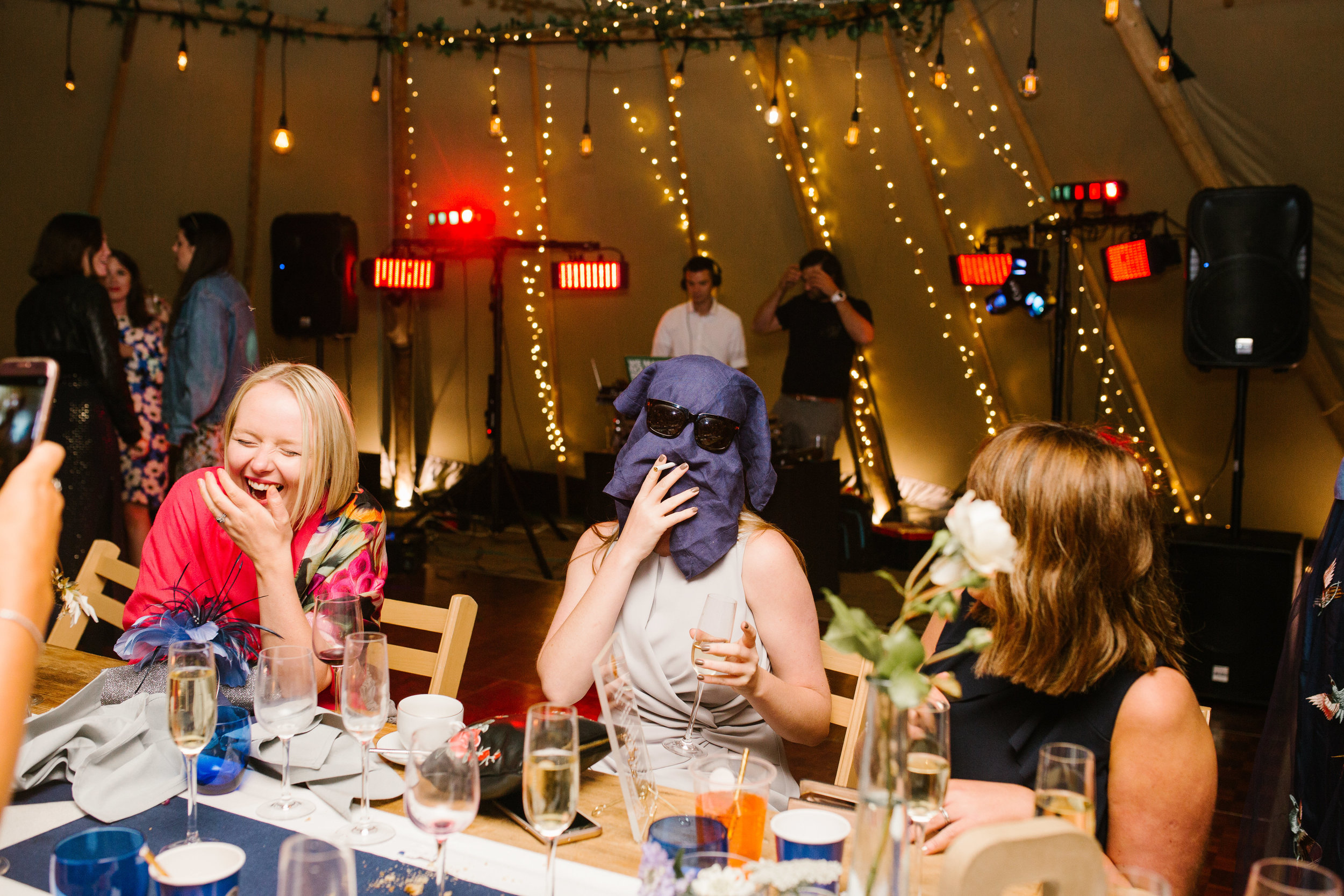 a candid photo of a wedding guest having fun with a napkn on her head as other guests laugh