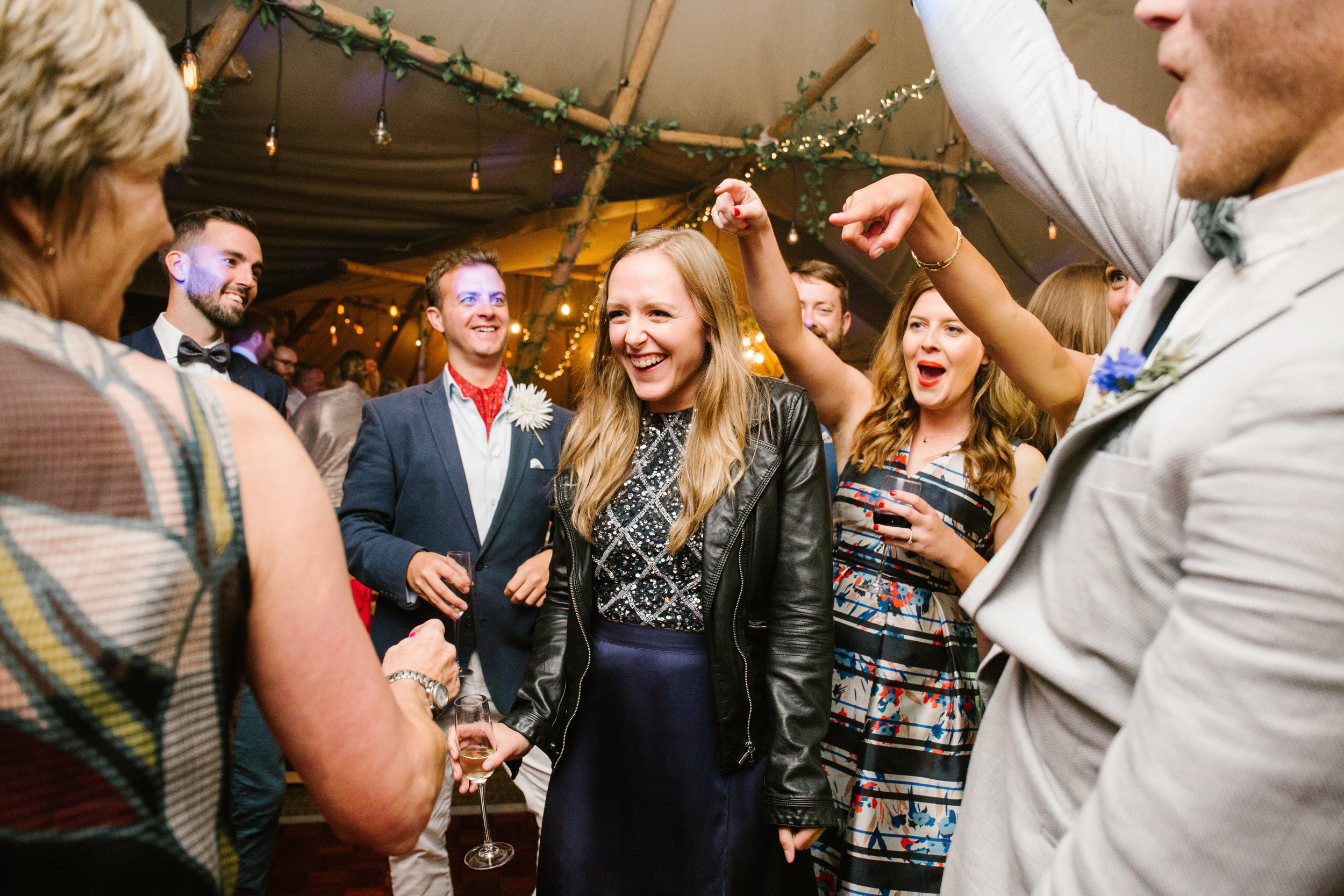 bridesmaid in the centre of the dance floor in a tipi while everyone points and cheers her on
