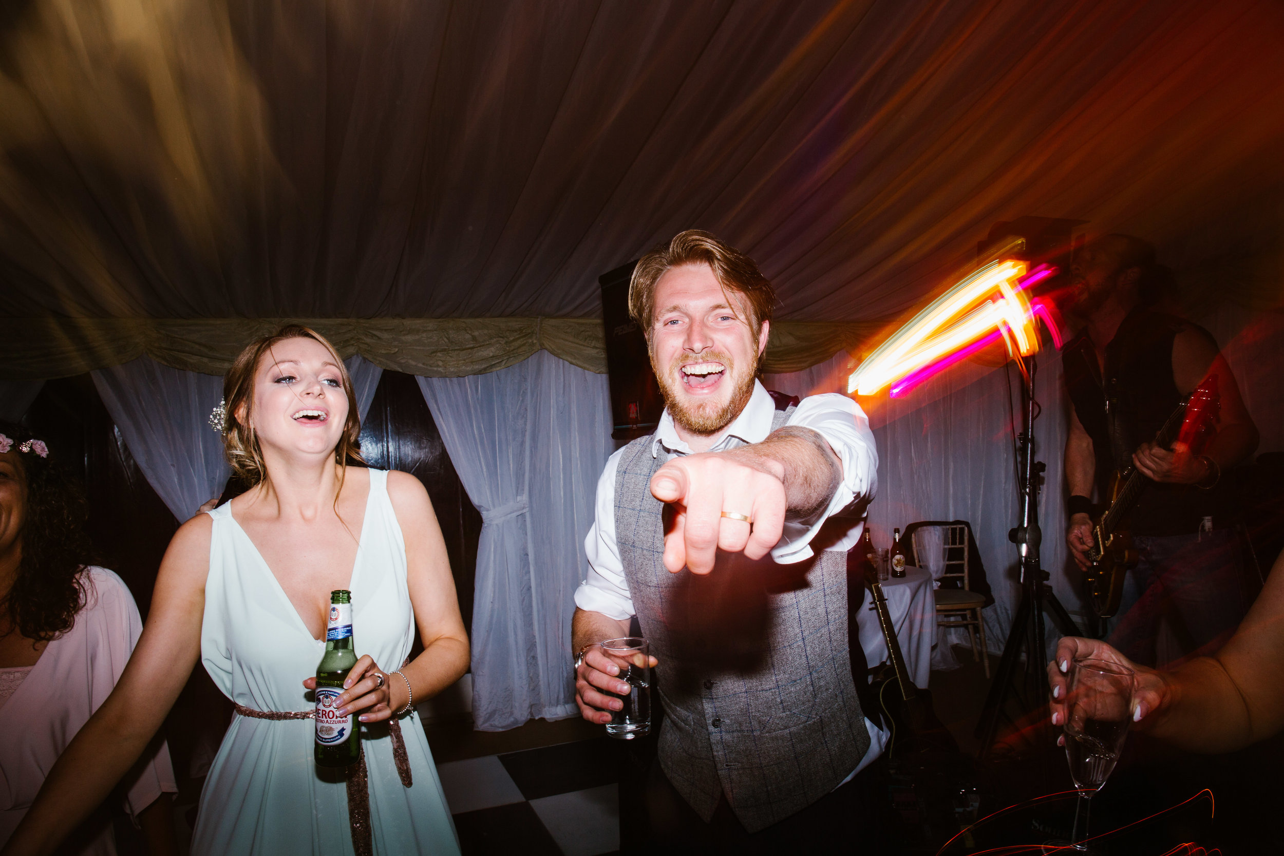 best man laughing on pointing on the dance floor of a marquee at a wedding in staffordshire