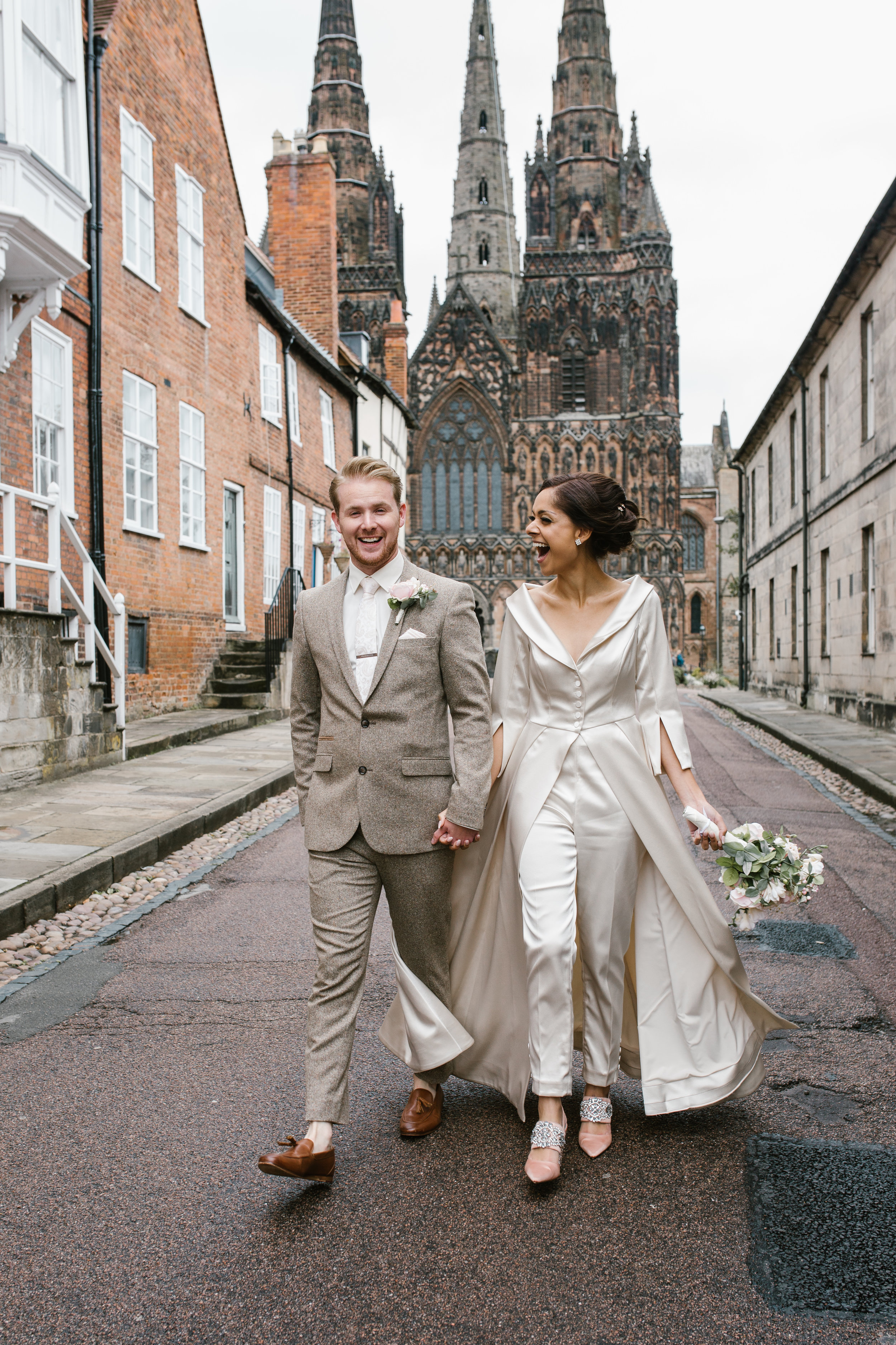 a very happy bride and groom walking holding hands laughing with lichfield cathedral in the background after their intimate ceremony- wedding photography in staffordshire