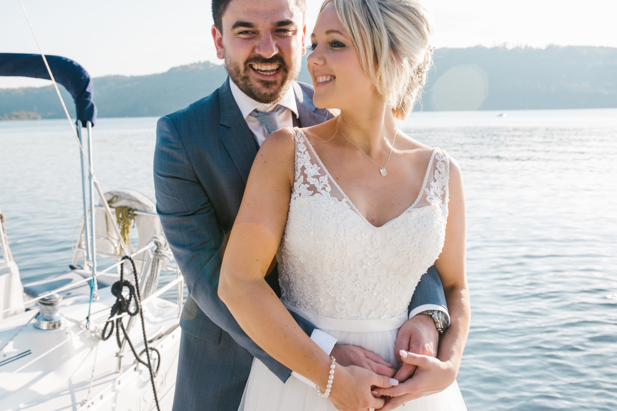 natural picture of newlyweds as they cuddle on a dock in the lake district with the blazing sunshine behind them on the lake windermere- lake district elopement photographer