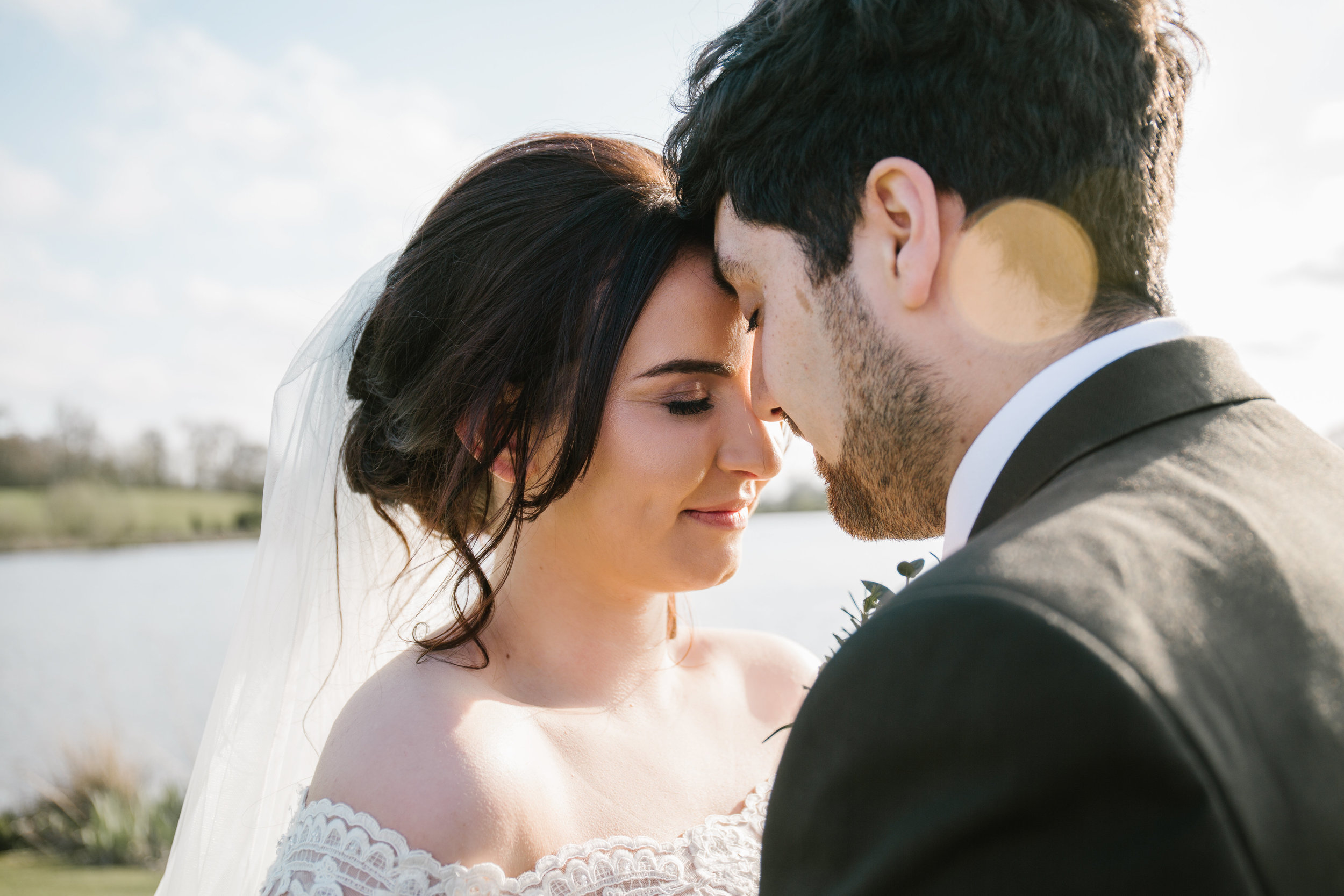a close up of a bride and grooms faces as they press tehir heads together and enjoy the golden sun on their wedding evening at sandhole oak barn