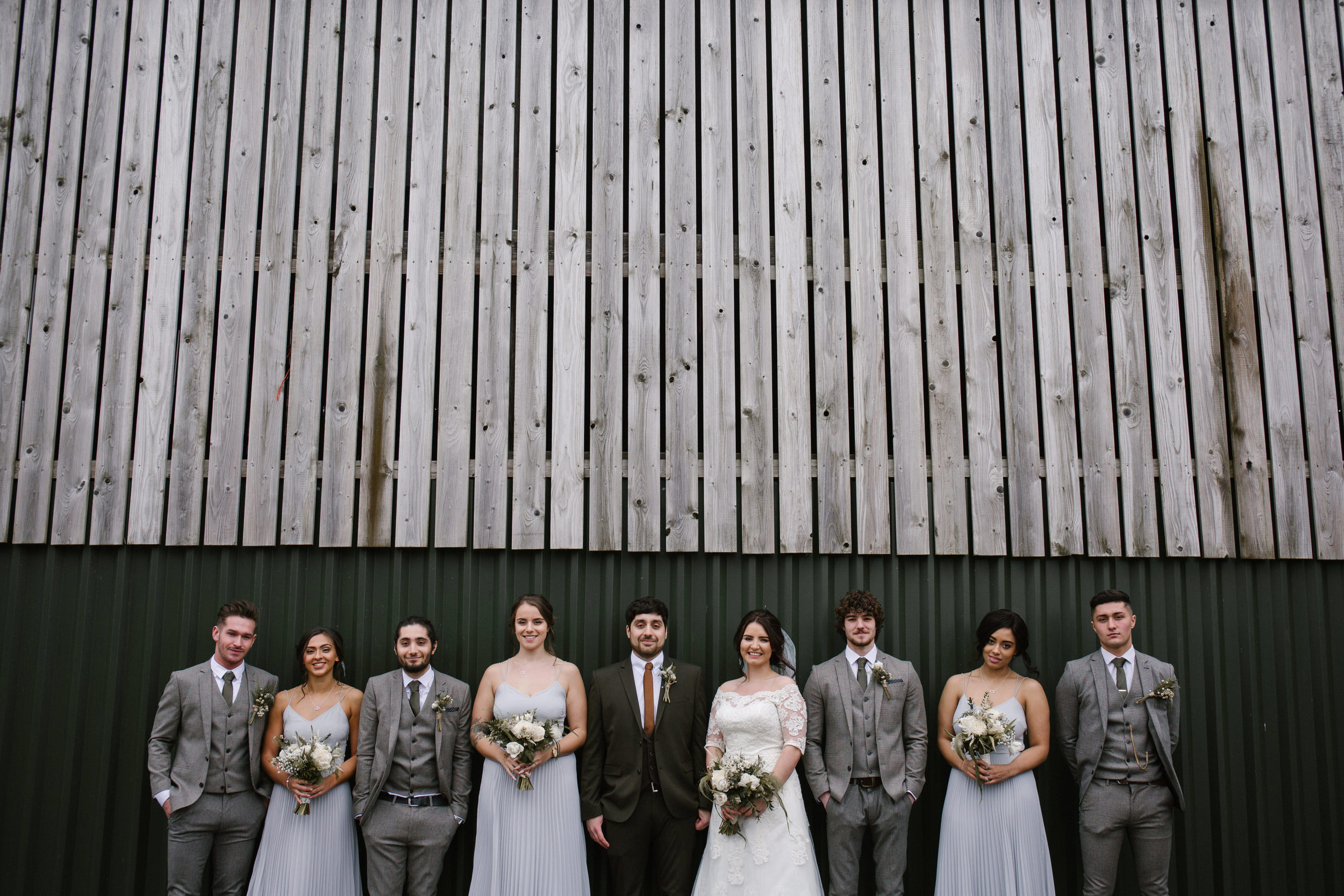 bridal party looking extra cool standing in front of a barn wall at sandhole oak barn in cheshire