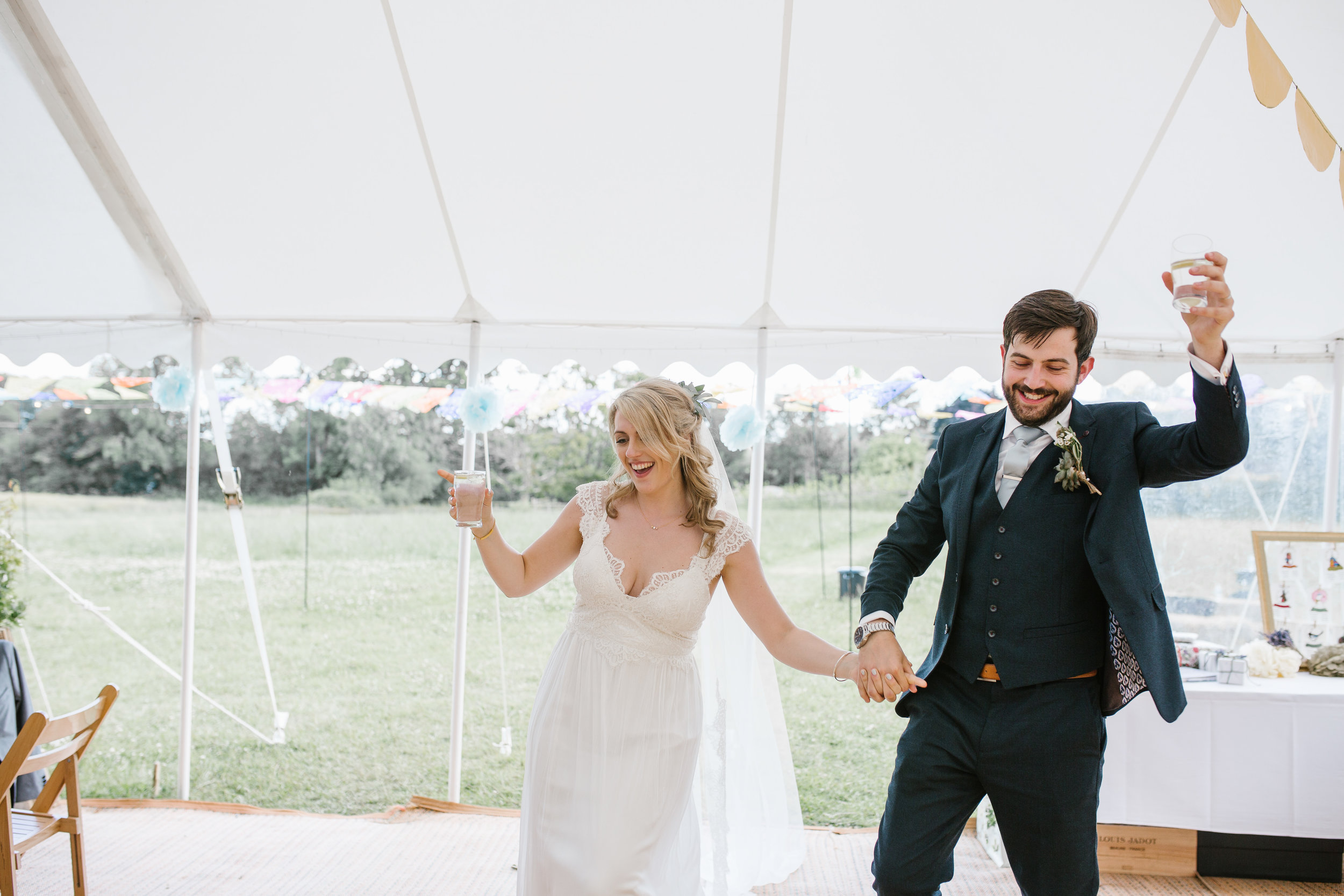 boho bride and groom enter the marquee holding hands and raising a gin in the other hand as they are welcomed by their guests at their festival wedding in the cotswolds
