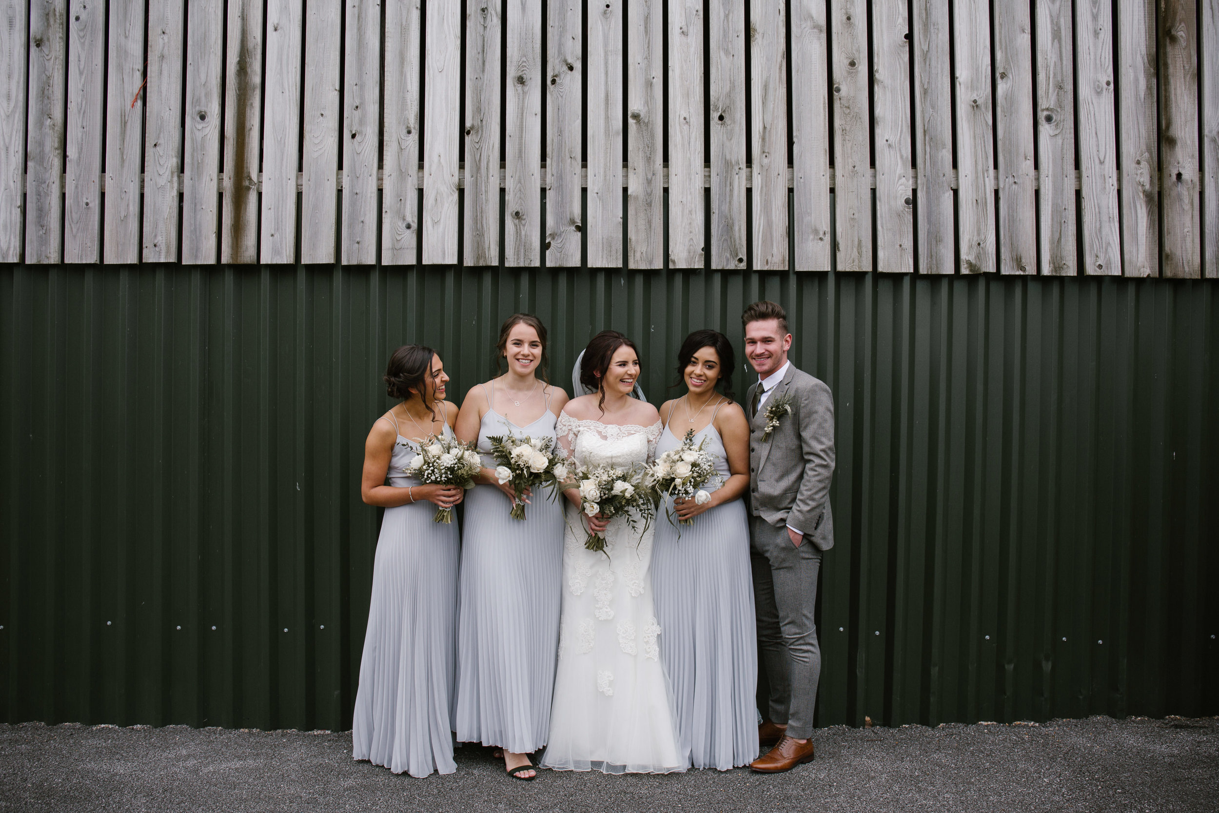 bridal squad standing in front of a barn wall at sandhole oak barn wearing asos