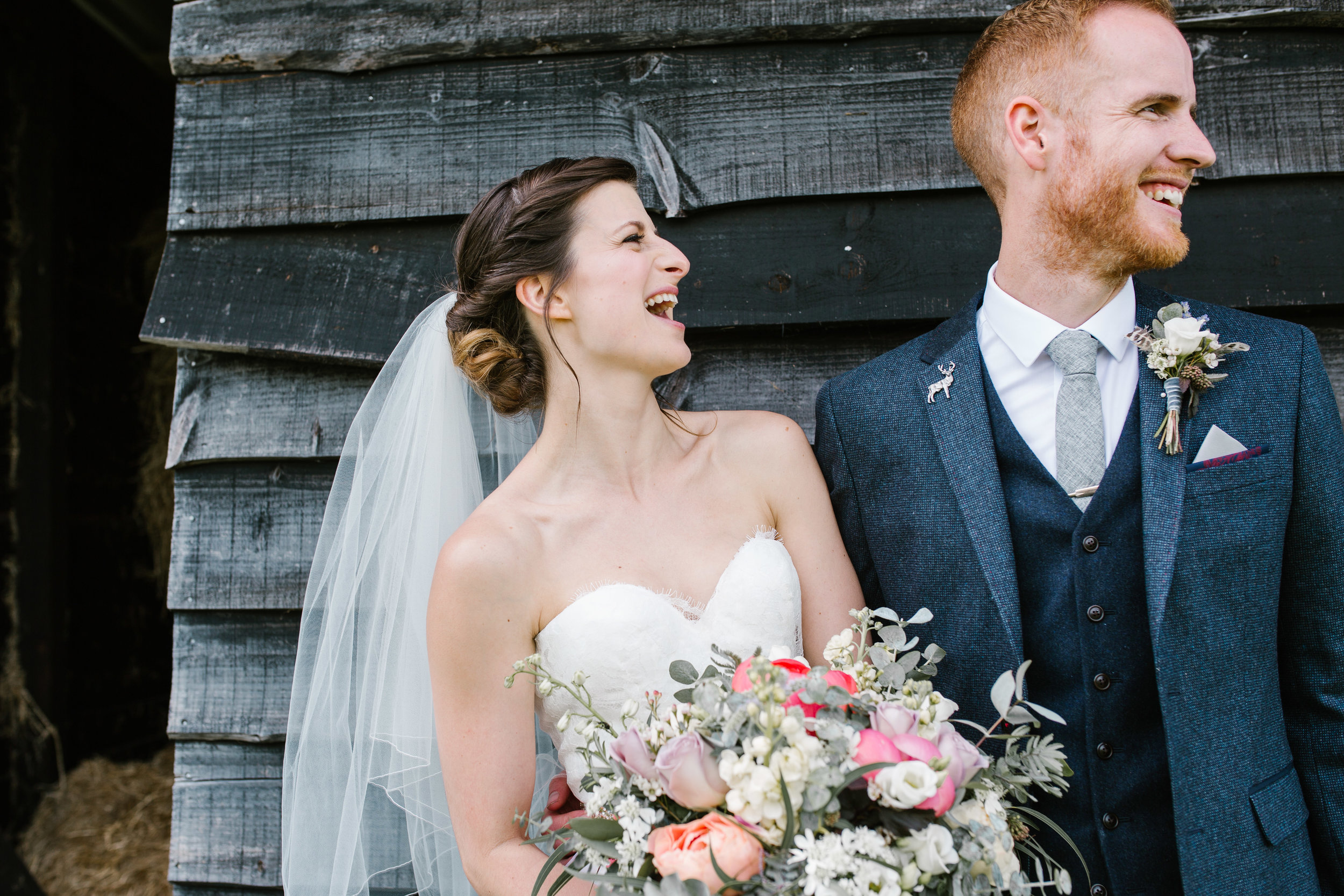 natural photo of bride laughing at her new husband at their rustic barn wedding in west sussex