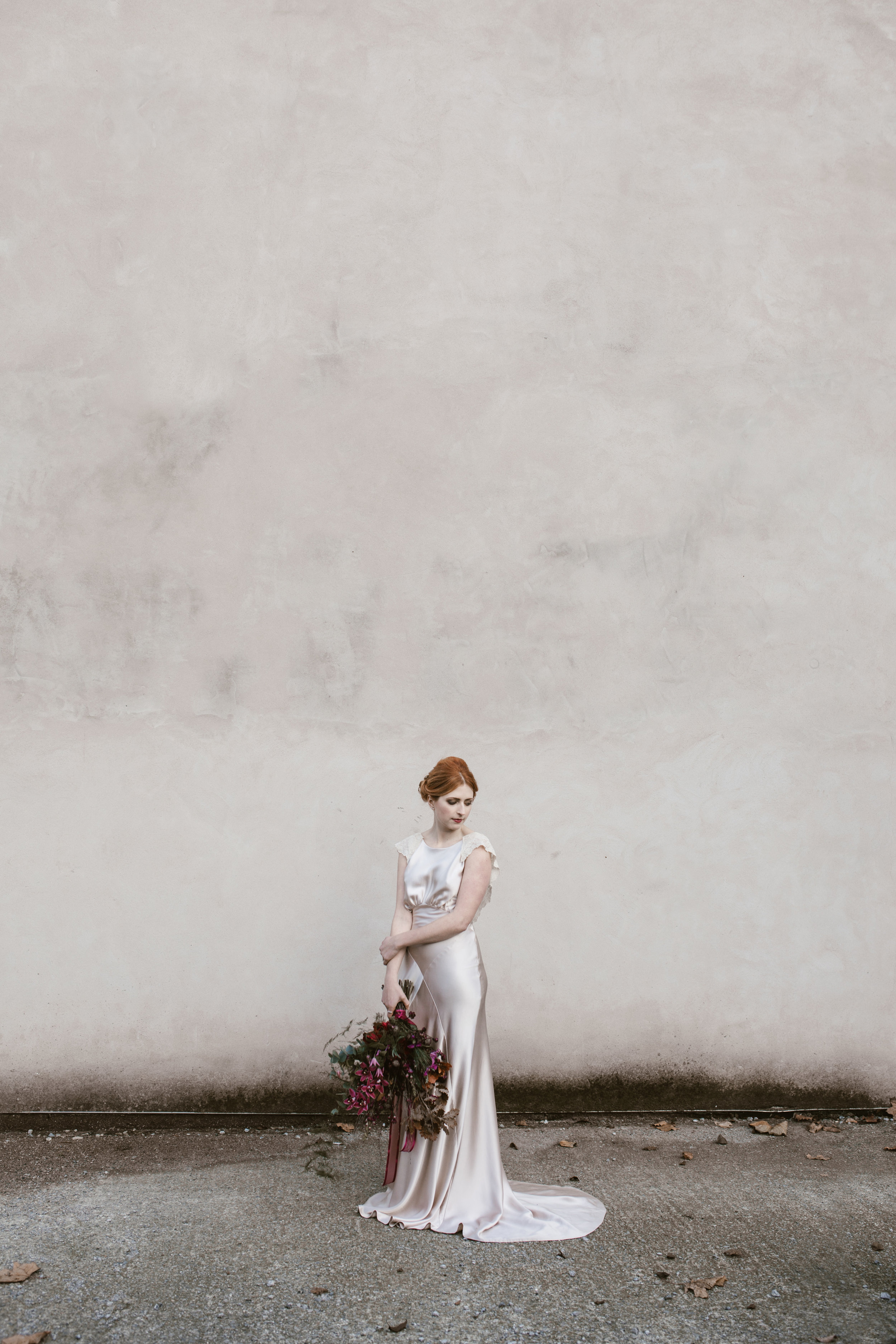 red headed bride stands against a concrete wall looking incredible holding red wild flowers