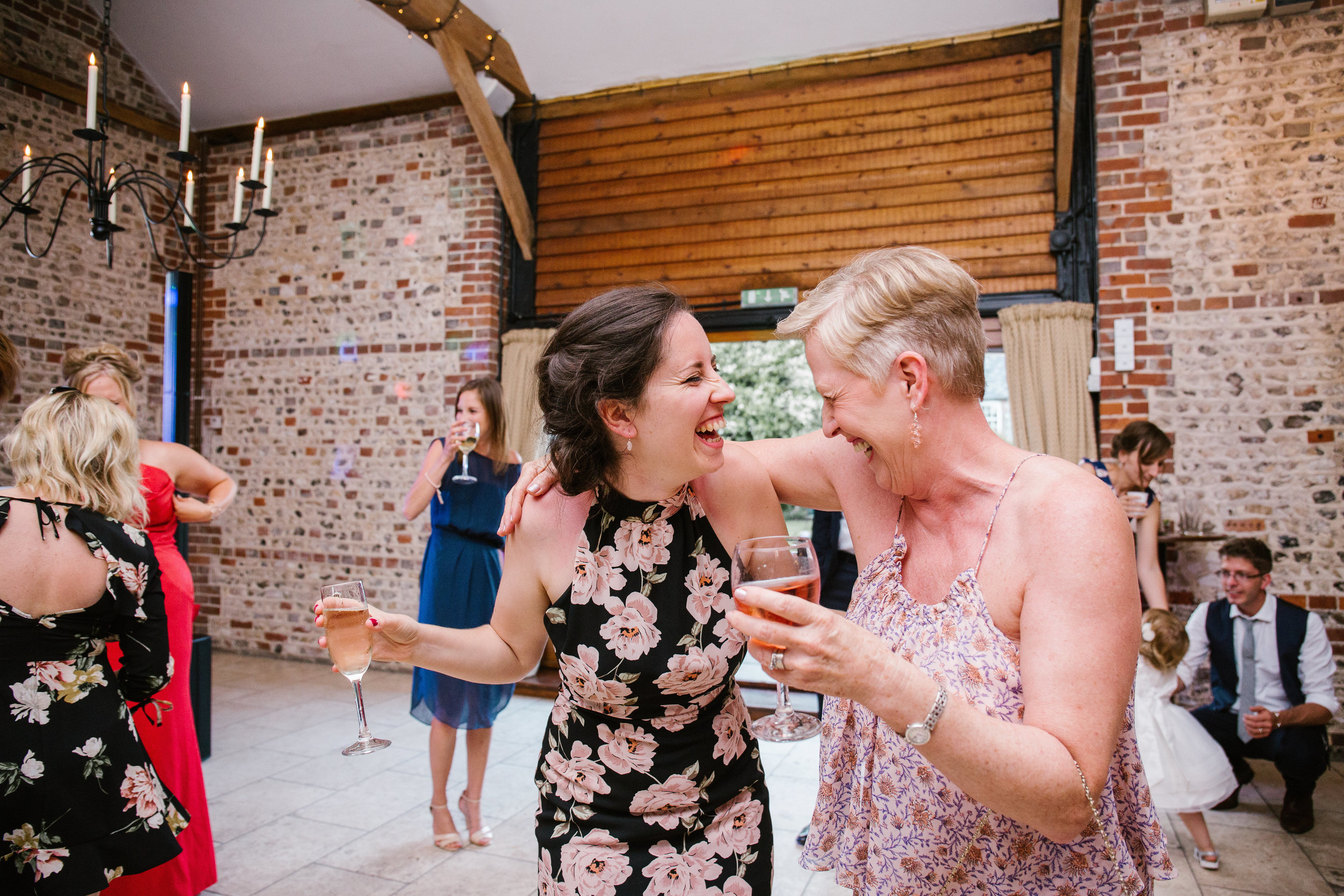 two ladies, at a summer wedding at upwaltham barns laugh together on the dance floor, drinking wine and hugging