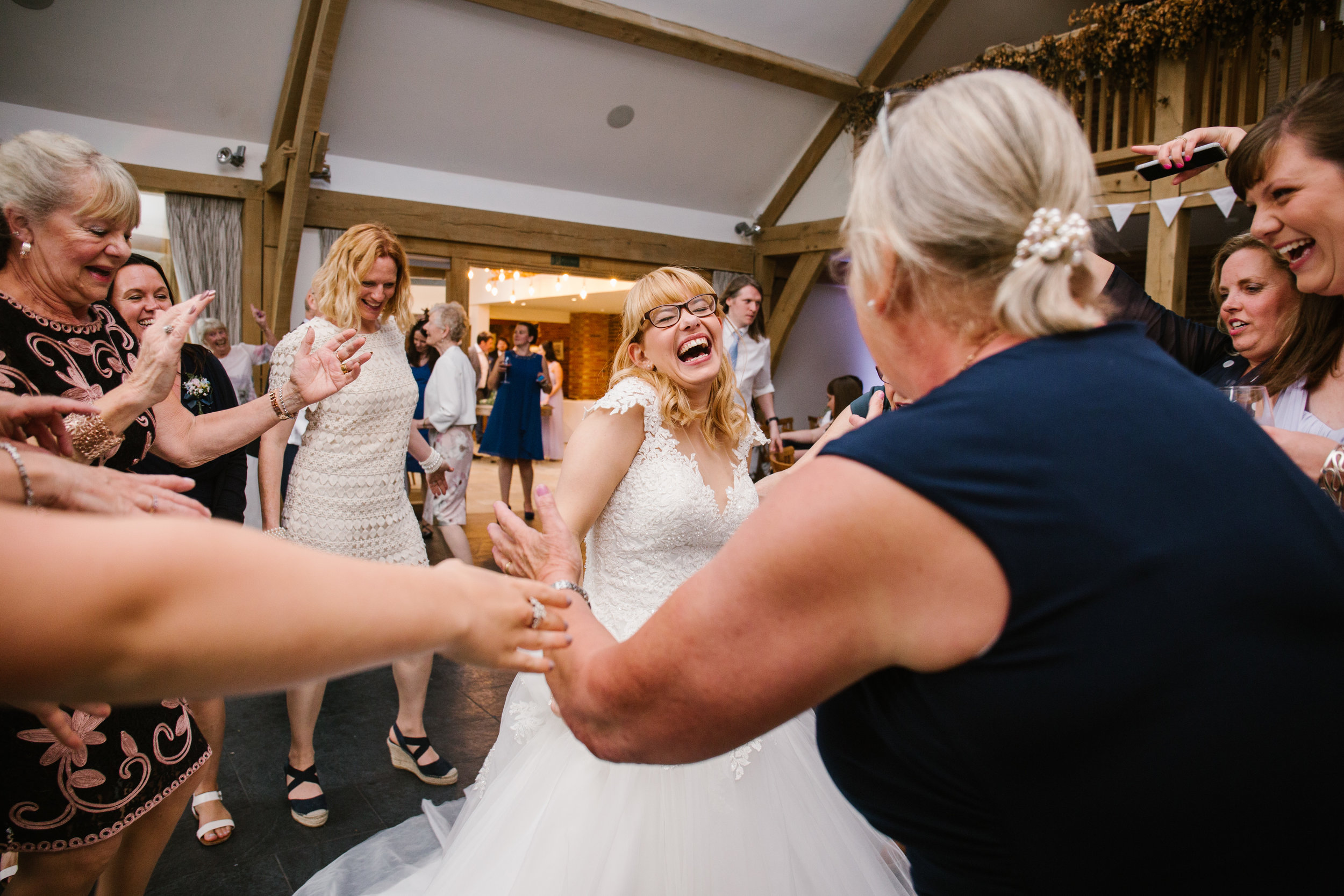 a documentary shot of bride laughing on the dance floor surrounded by her new family at mythe barn leicestershire