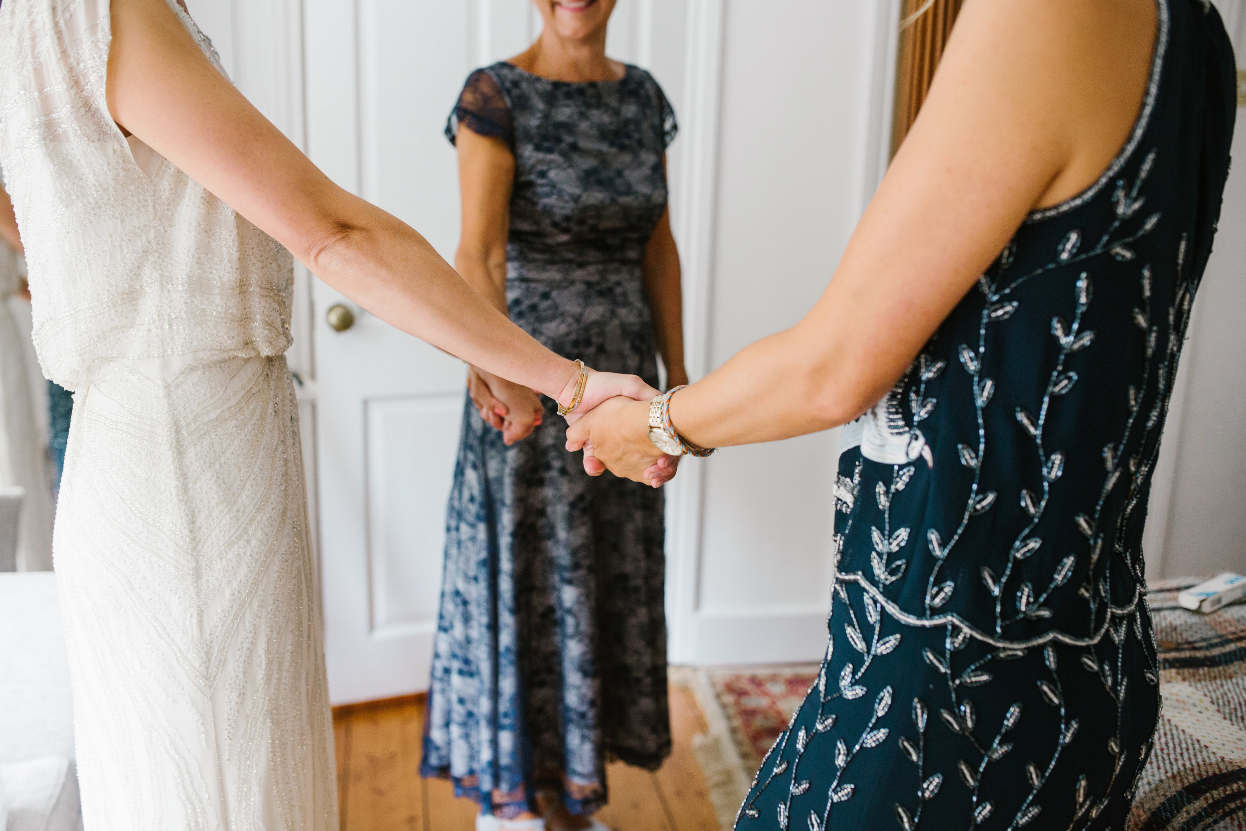 documentary close up photo of bride holding hands with her sister and mom on the morning of her wedding