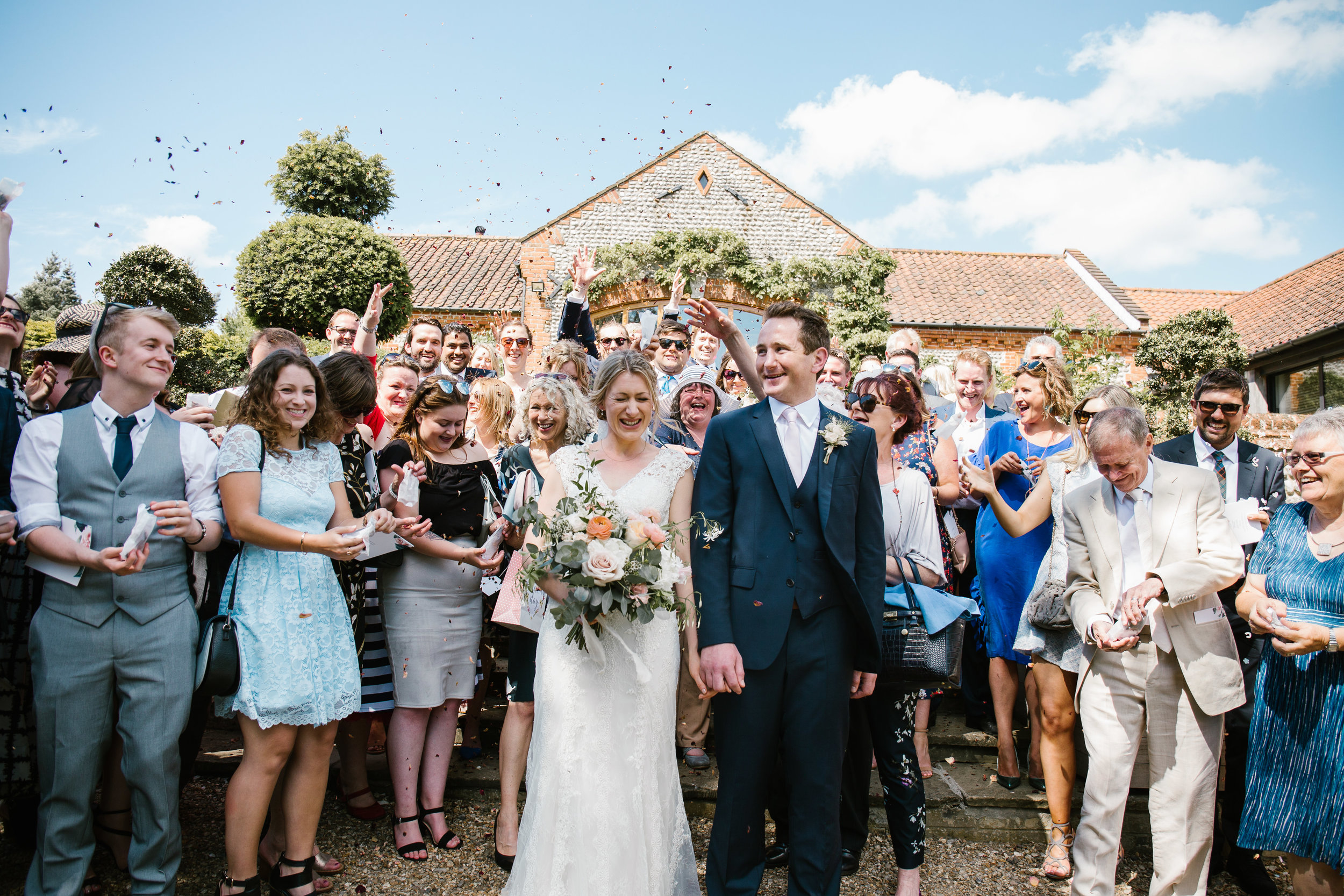 bride and groom are showered with lots of confetti from a crowd of guests after their ceremony at chaucer barns- norfolk