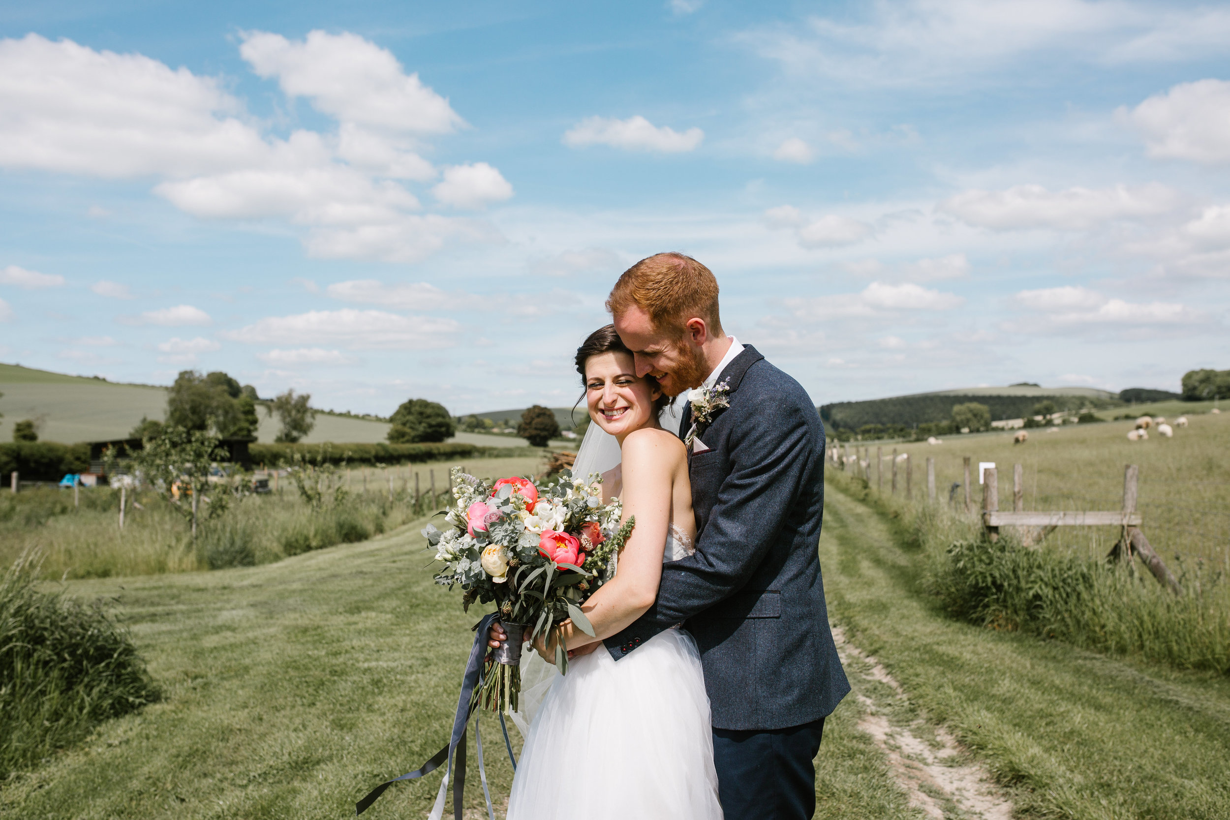 summer wedding at upwaltham barns as the bride and groom cuddle up close together