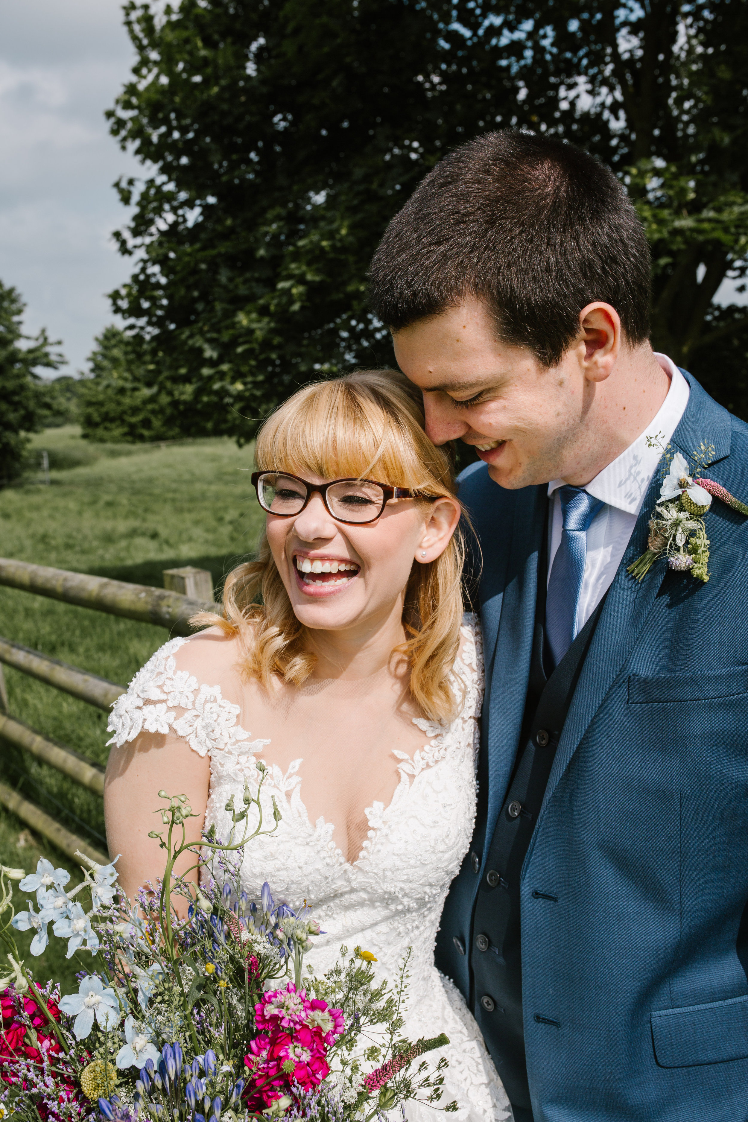 fun photo of bride and groom laughing together at their summer wedding at mythe barn- staffordshire wedding photographer