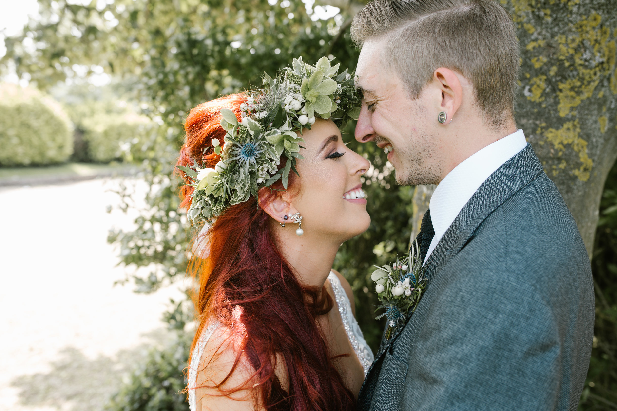 amazing flower crown being worn by a red headed bride, laughing with her new husband in the summer sun- relaxed wedding photography