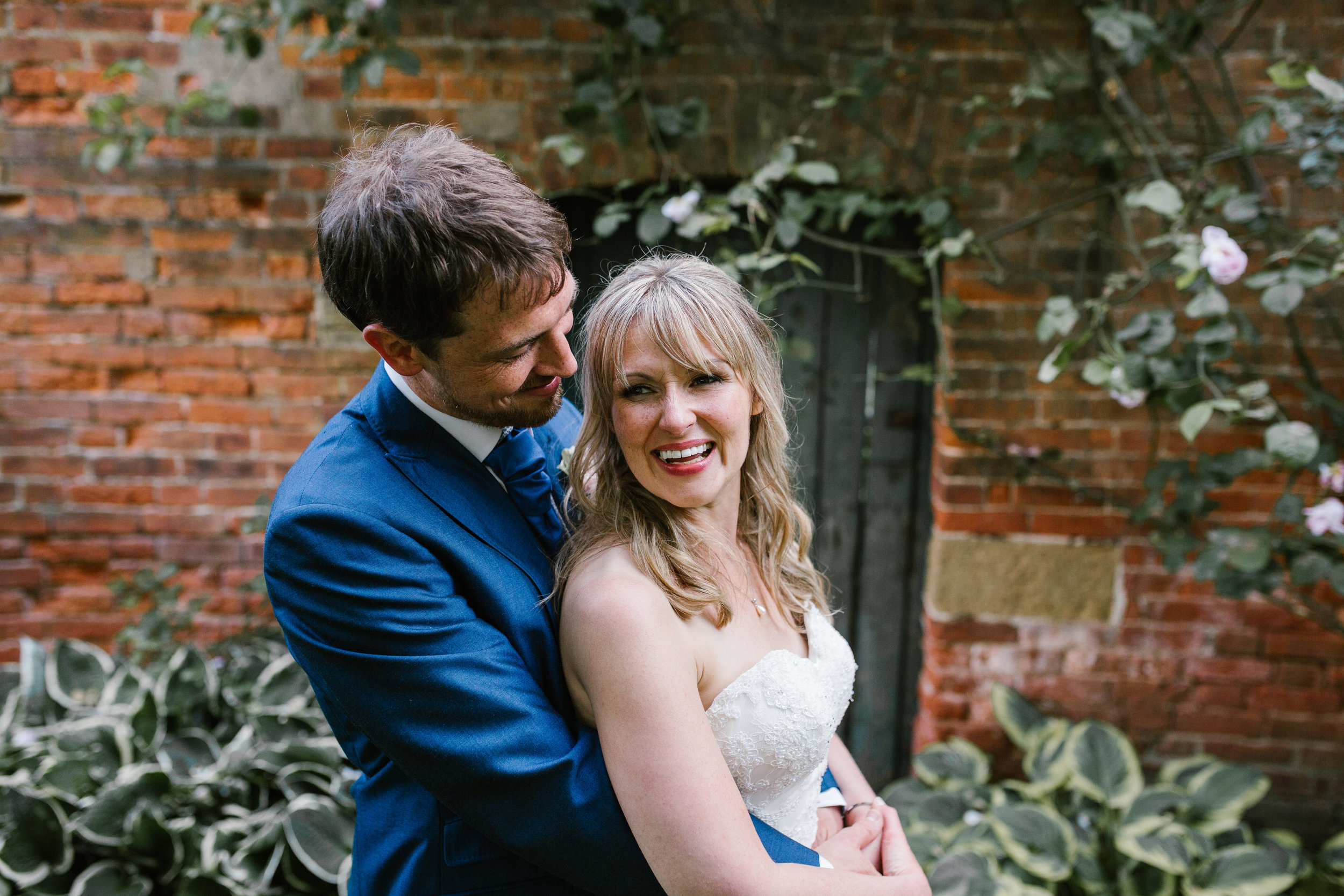 natural photo of bride and groom hugging together in the grounds of the walled garden at beeston fields- nottingham wedding photography
