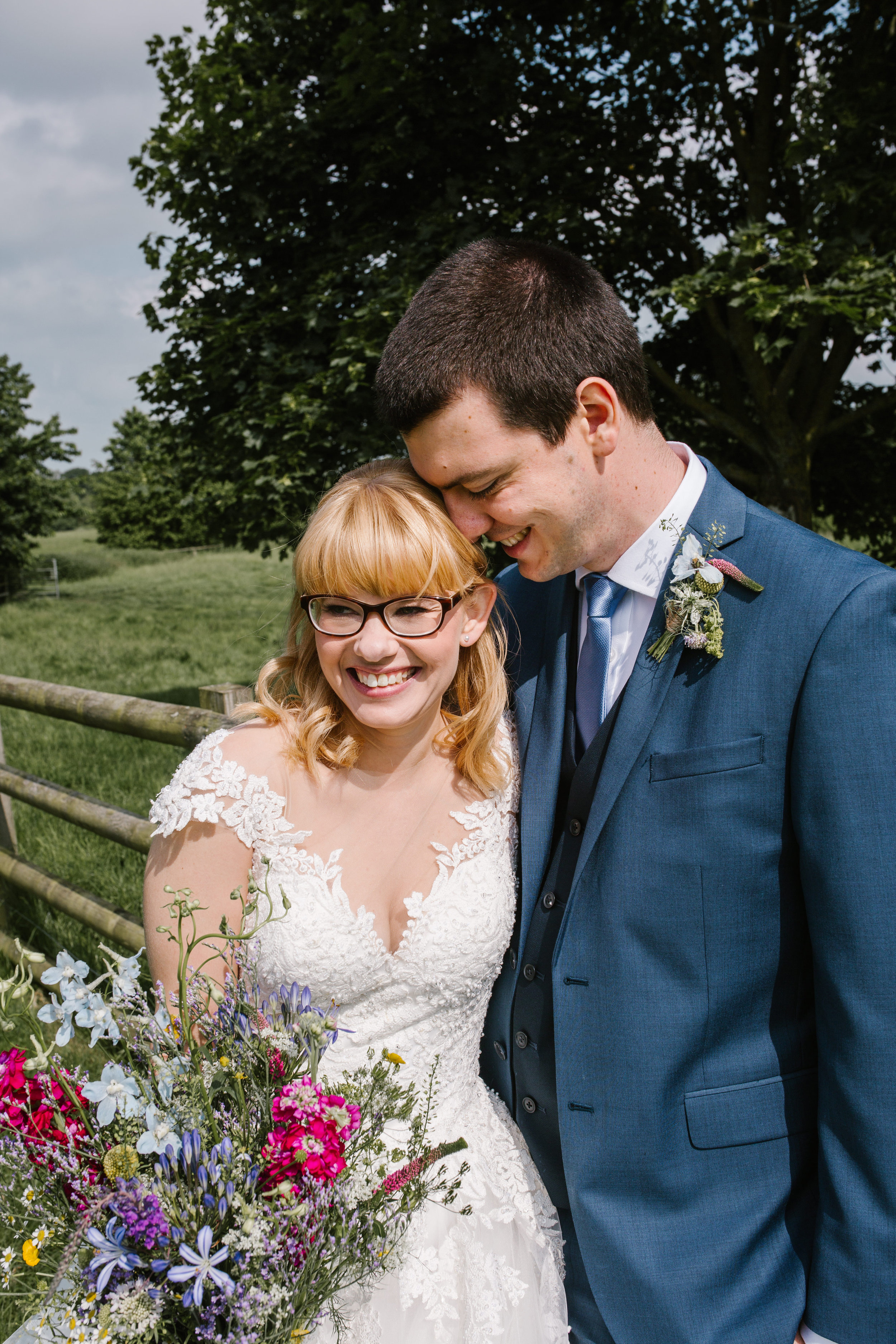 natural picture of bride and groom laughing at their summer wedding at mythe barn- leicestershire wedding photography