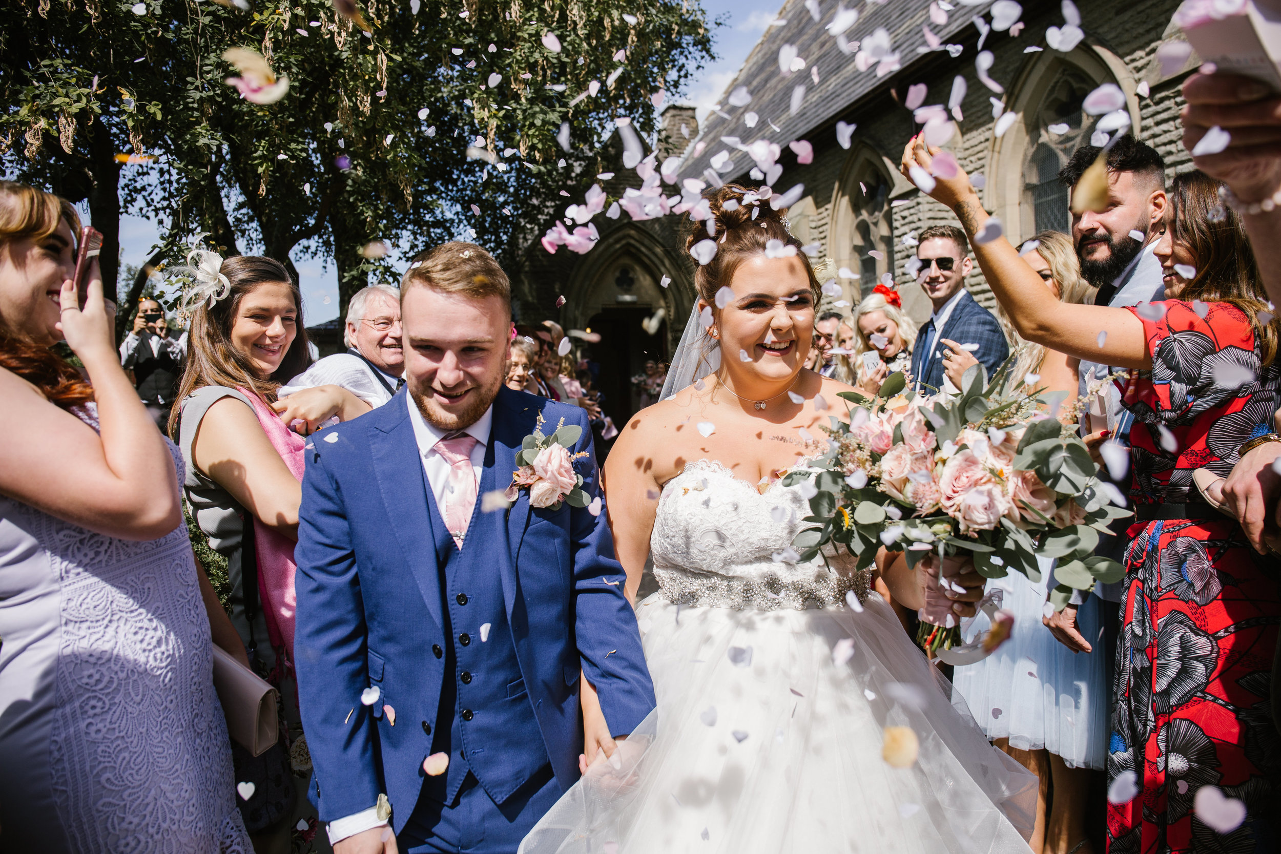 pink confetti gets thrown at bride and groom after their wedding ceremony in manchester