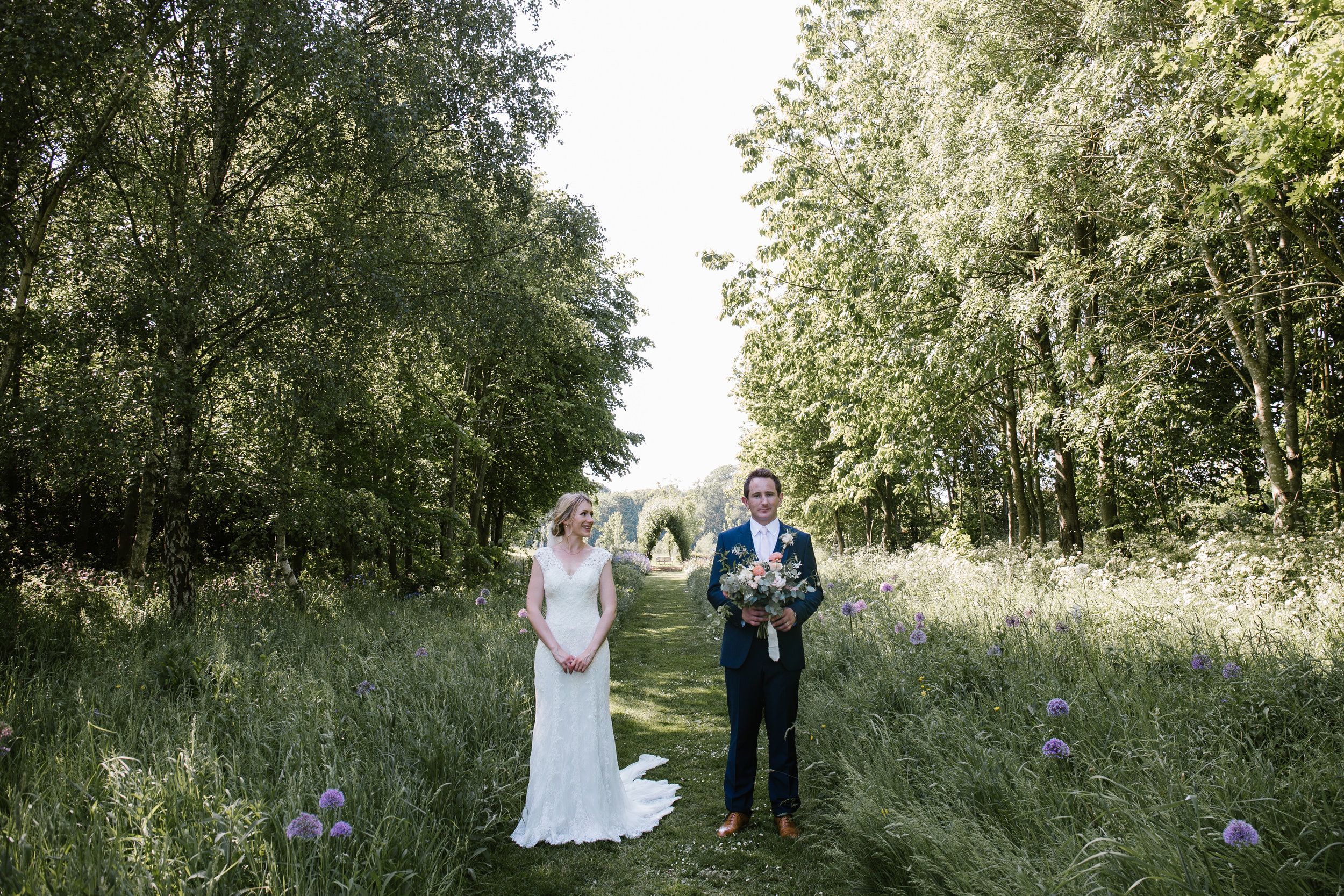 quirky photo of bride and groom at chaucer barns, the groom holds the wedding flowers