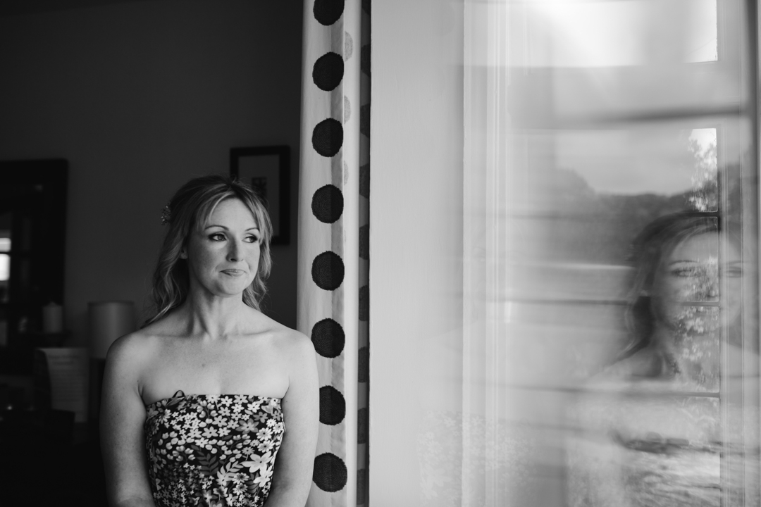 natural black and white photo of bride looking out the window on the morning of her wedding- nottingham wedding