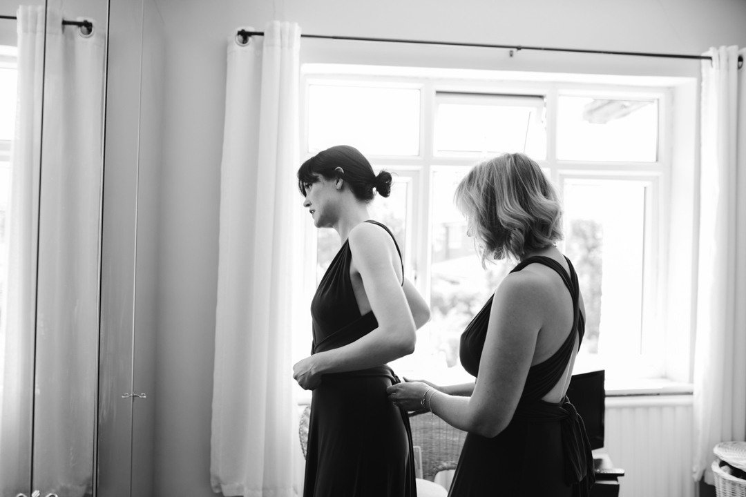 black and white photo of bridesmaids tying up each others dress