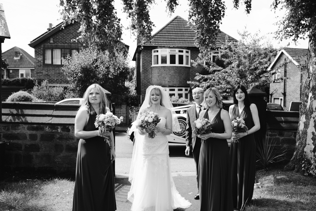 natural black and white photo of bride, father of the bride and bridesmaids arriving at the church - nottingham wedding