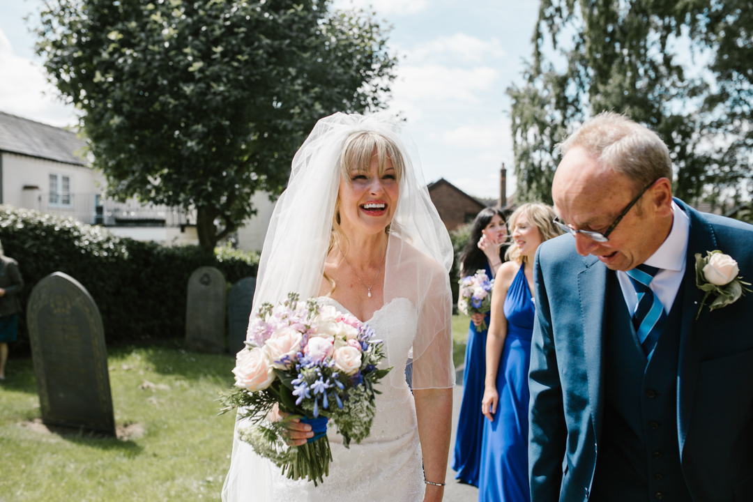 bright fun photo of bride laughing with her dad just before walking into the church to get married