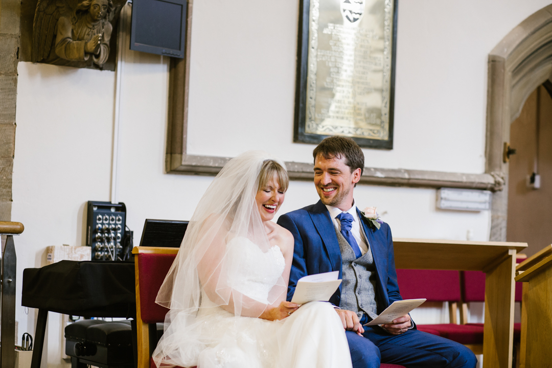 bride and groom laughing together in the church during their wedding ceremony- nottingham wedding