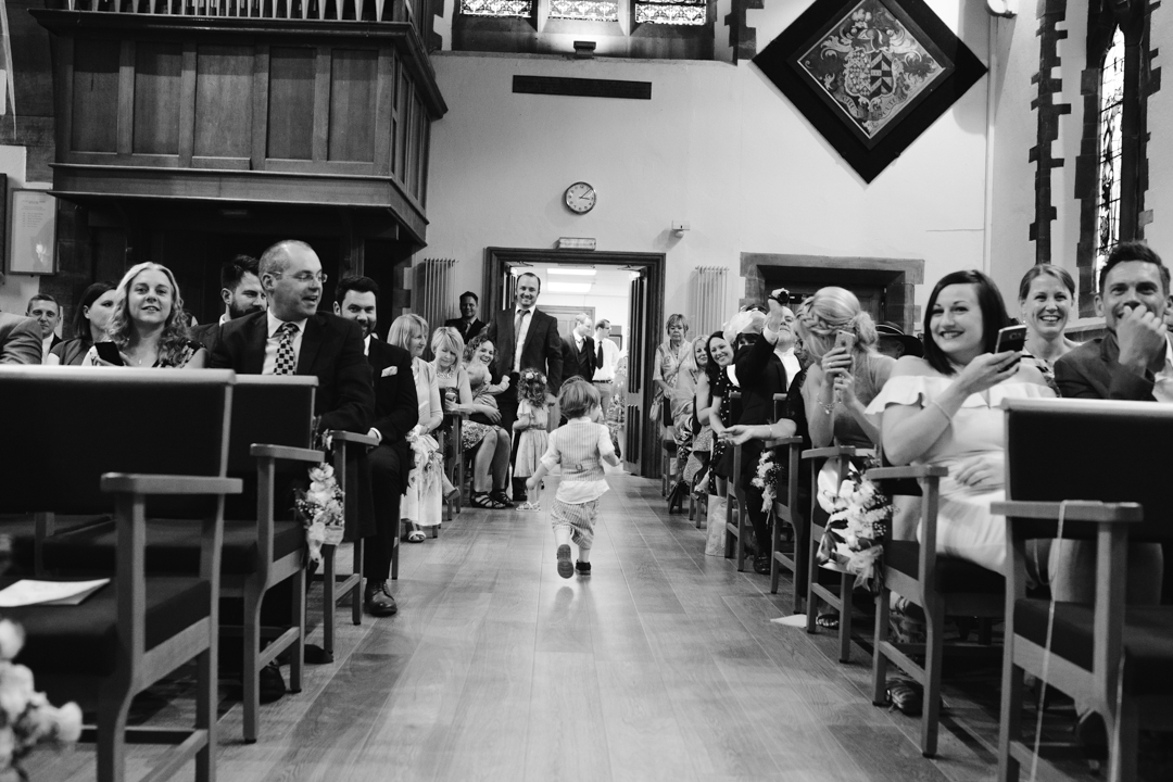 black and white photo of child running down the aisle in the church at a wedding in nottingham