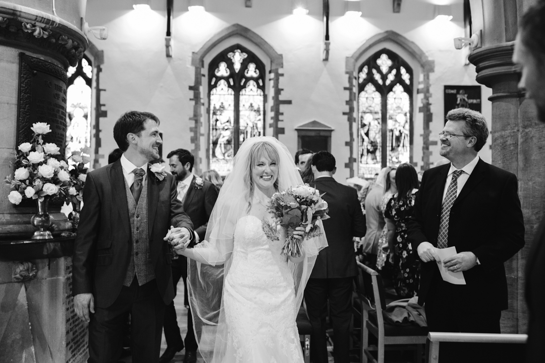 black and white natural photo of bride and groom walking down the aisle after becoming husband and wife