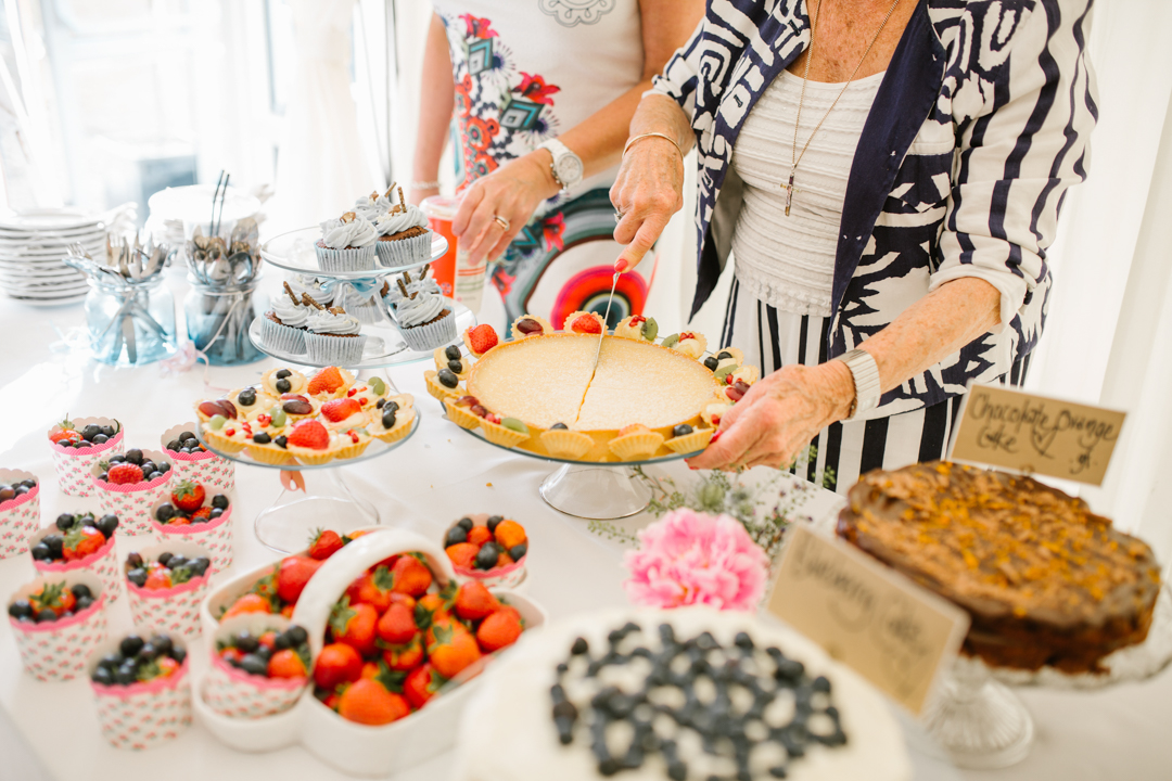 cutting the cheesecake on a dessert table full of homemade dessert at laid back wedding in nottingham