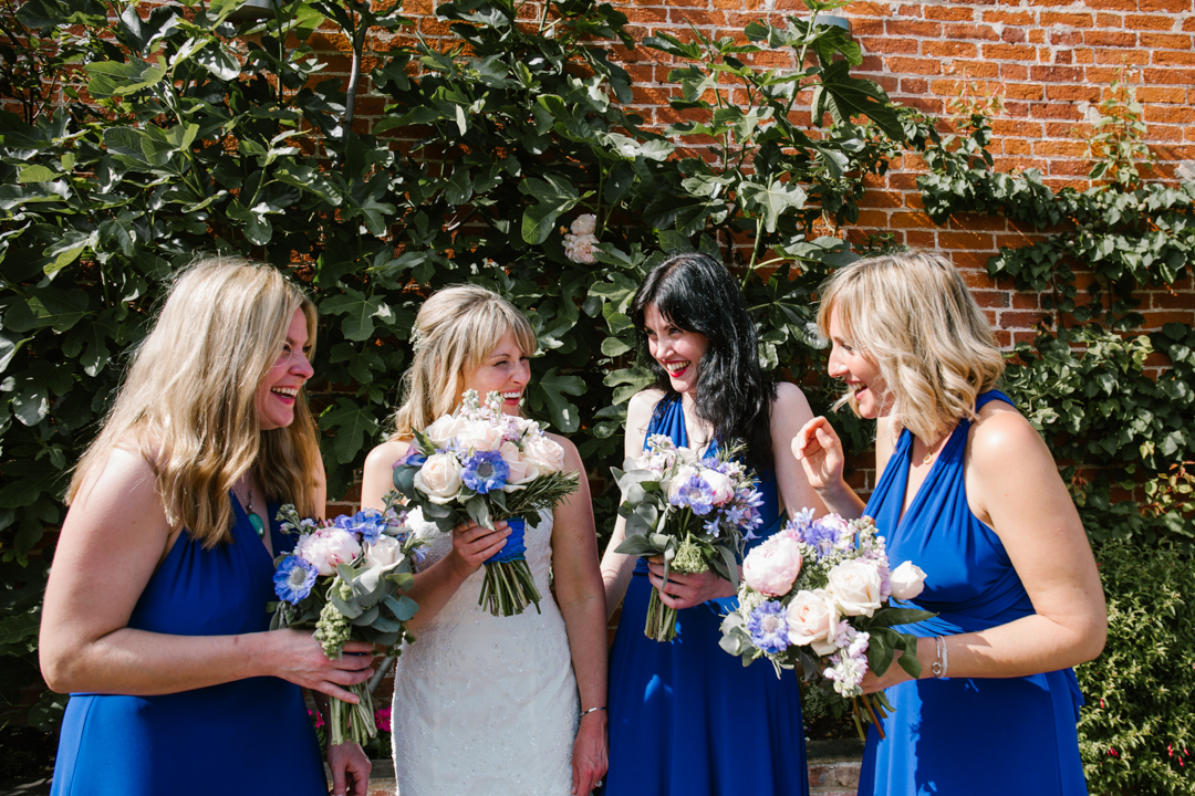natural fun photo of bridesmaids and bride laughing together at the wedding reception at the walled garden in nottingham