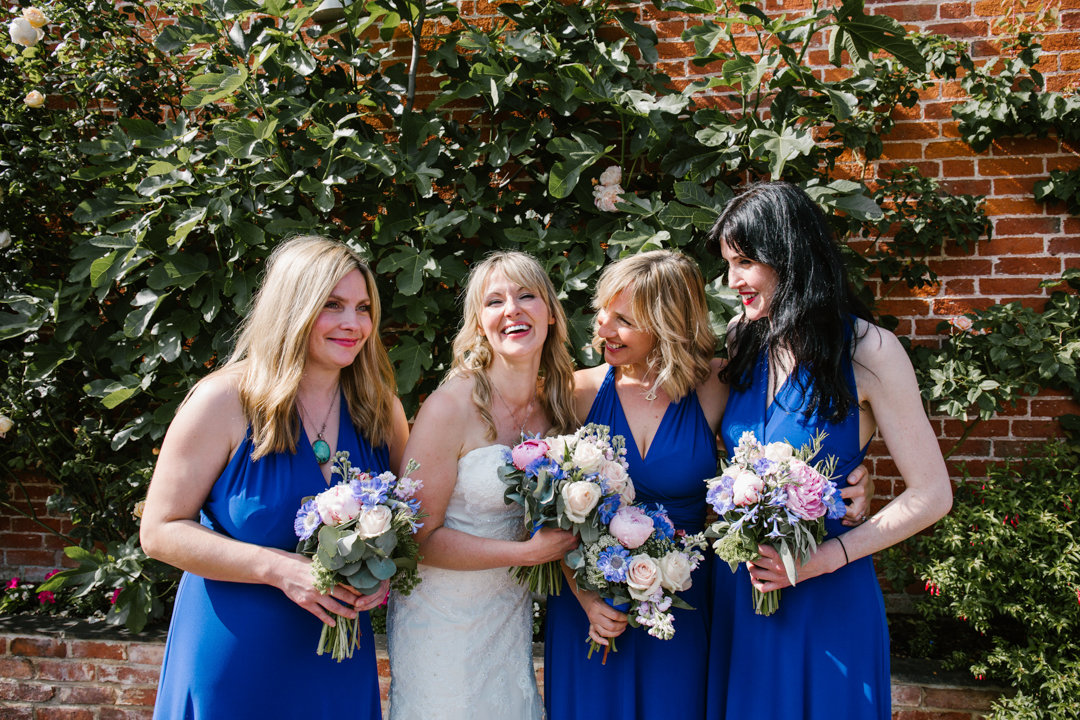 natural photo of bride and bridesmaids dressed in navy blue, laughing together in the courtyard at the walled garden in beeston fields
