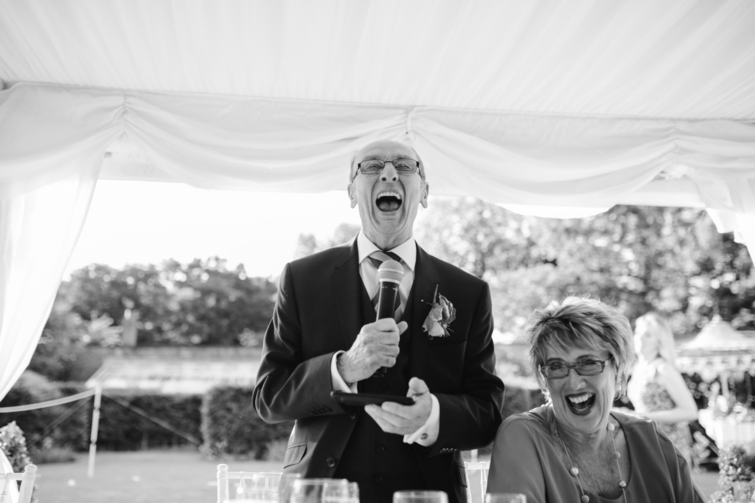 fun black and white photo of father of the bride laughing while reading his speech