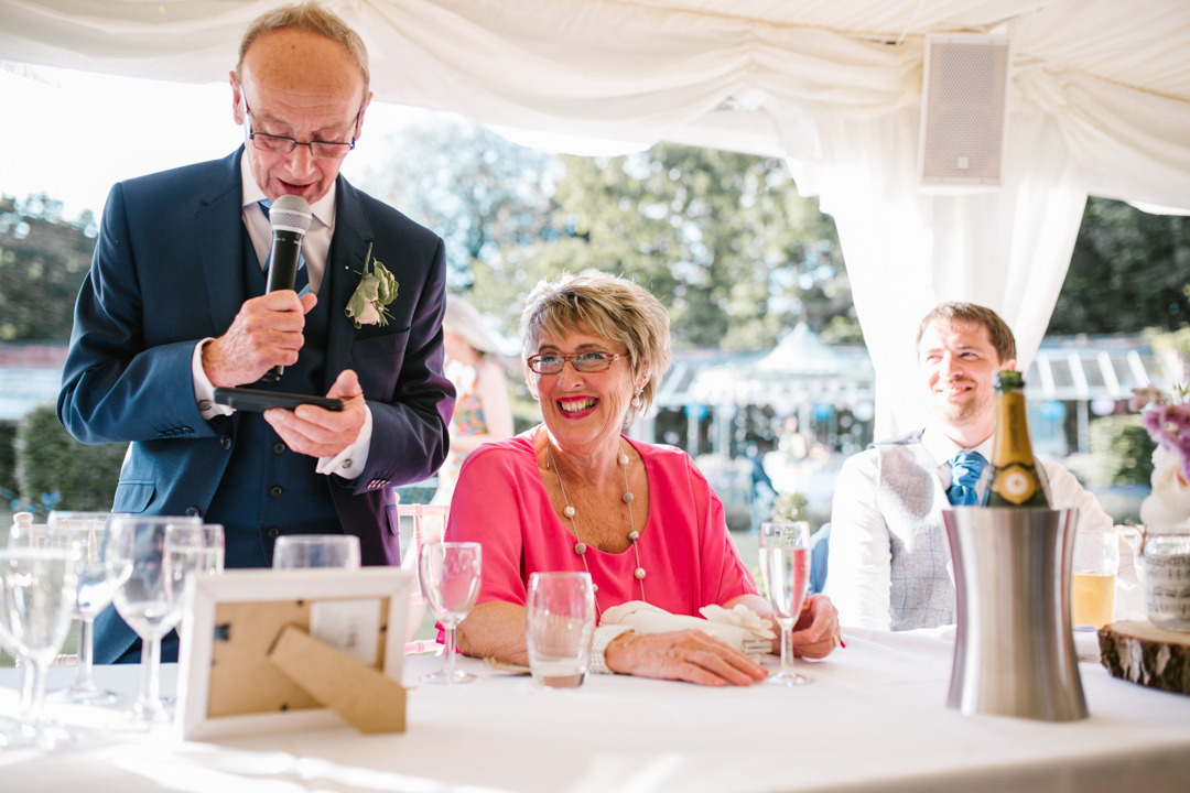 bright photo of wedding speeches in the walled garden at beeston fields, mother of the bride laughing at the father of the bride