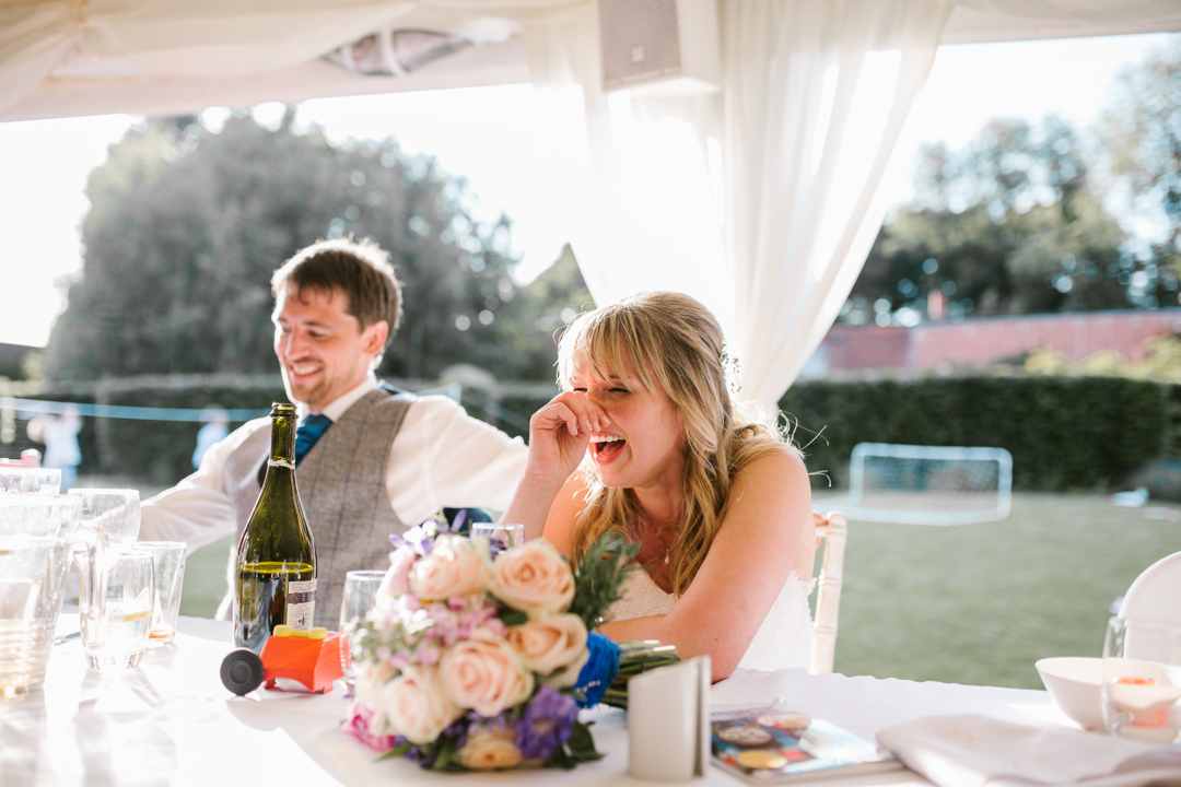 documentary photo of bride laughing during wedding speeches in the marquee at the walled garden in nottingham