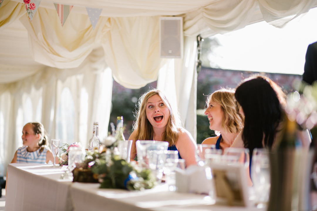 bridesmaid laughing during the wedding speeches