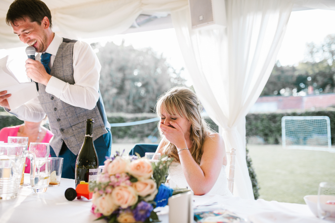 bright and natural photo of bride laughing while the groom does his wedding speech