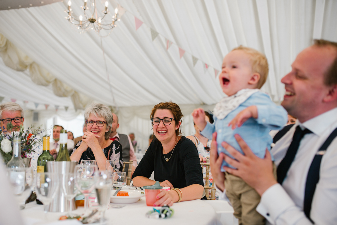 documentary photo of wedding guests and baby laughing during the wedding speeches- nottingham wedding photographer